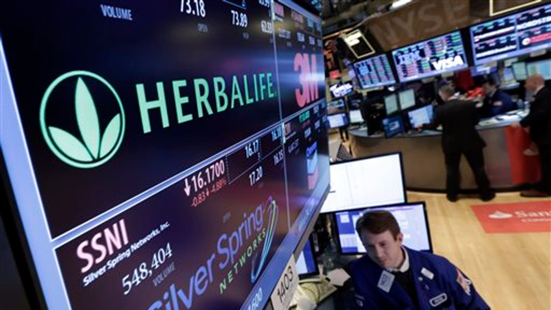Specialist Peter Elkins foreground, works at the post that handles Herbalife, on the floor of the New York Stock Exchange, Thursday, Jan. 23, 2014. Herbalife Ltd. shares fell Thursday after U.S. Sen. Edward Markey called for an investigation into the company's business practices. (AP Photo/Richard Drew)