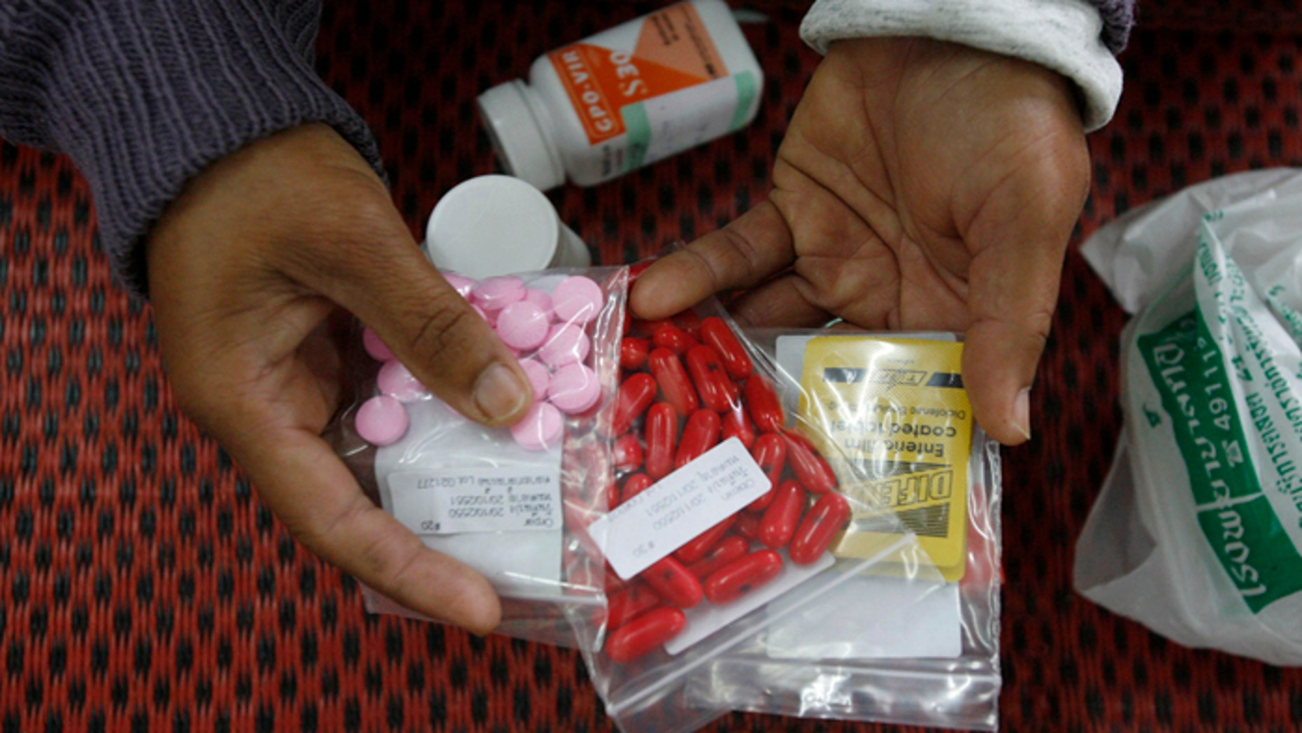 An HIV-infected patient displays medicine at a hospital in Payao province, about 373 miles north of Bangkok.