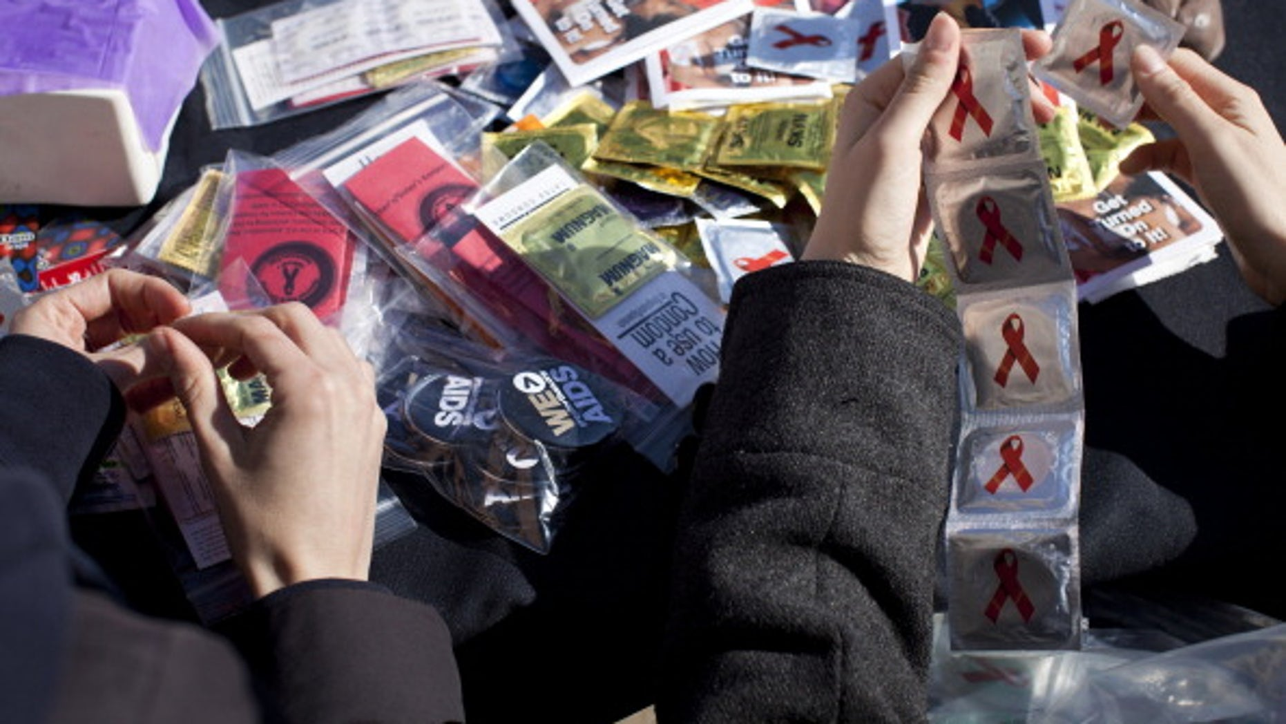 Volunteers separate condoms to give away during a free HIV testing event .