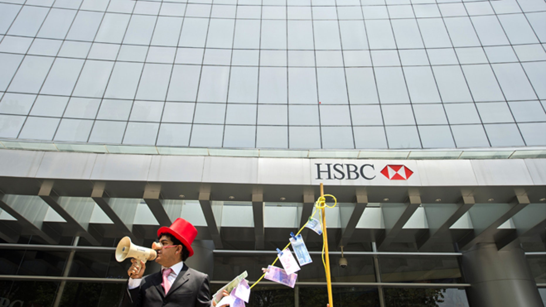 """A man weraing a pig nose and holding fake notes shouts slogans during a protest in front of a HSBC branch building, in Mexico City on July 30, 2012. HSBC said on July 30 it took a provision of 700 USD million (571 million euros) to cover fines for failing to apply anti-money laundering rules and warned the overall cost could be """"significantly higher."""" AFP PHOTO/Alfredo ESTRELLA        (Photo credit should read ALFREDO ESTRELLA/AFP/GettyImages)"""