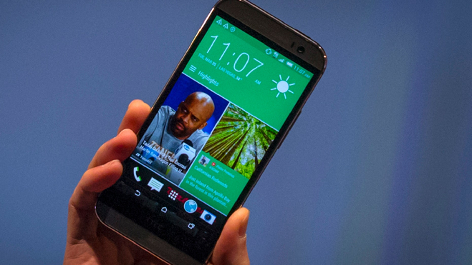 March 25, 2014: HTC CEO Peter Chou shows the new HTC One M8 phone during a launch event in New York.