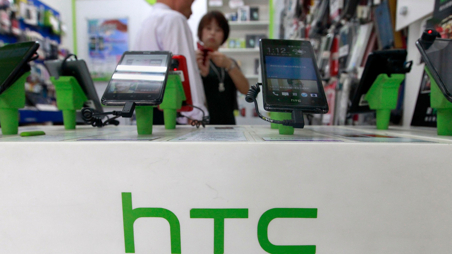 Customers look at HTC smartphones in a mobile phone shop in Taipei July 30, 2013. Taiwan's HTC Corp expects revenue to fall as much as 30 percent in the third quarter compared to the previous three months, far below analysts' forecasts. REUTERS/Pichi Chuang (TAIWAN - Tags: BUSINESS TELECOMS) - RTX124KL