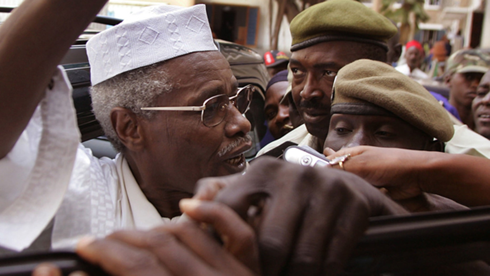 In this Friday, Nov. 25, 2005, file photo,  Former Chad dictator Hissene Habre, left,  seen as he leaves the court in Dakar, Senegal. A French lawyer for ex-Chadian dictator Hissene Habre confirms he has been charged with war crimes, crimes against humanity and torture by a special court set up in Senegal to try him.