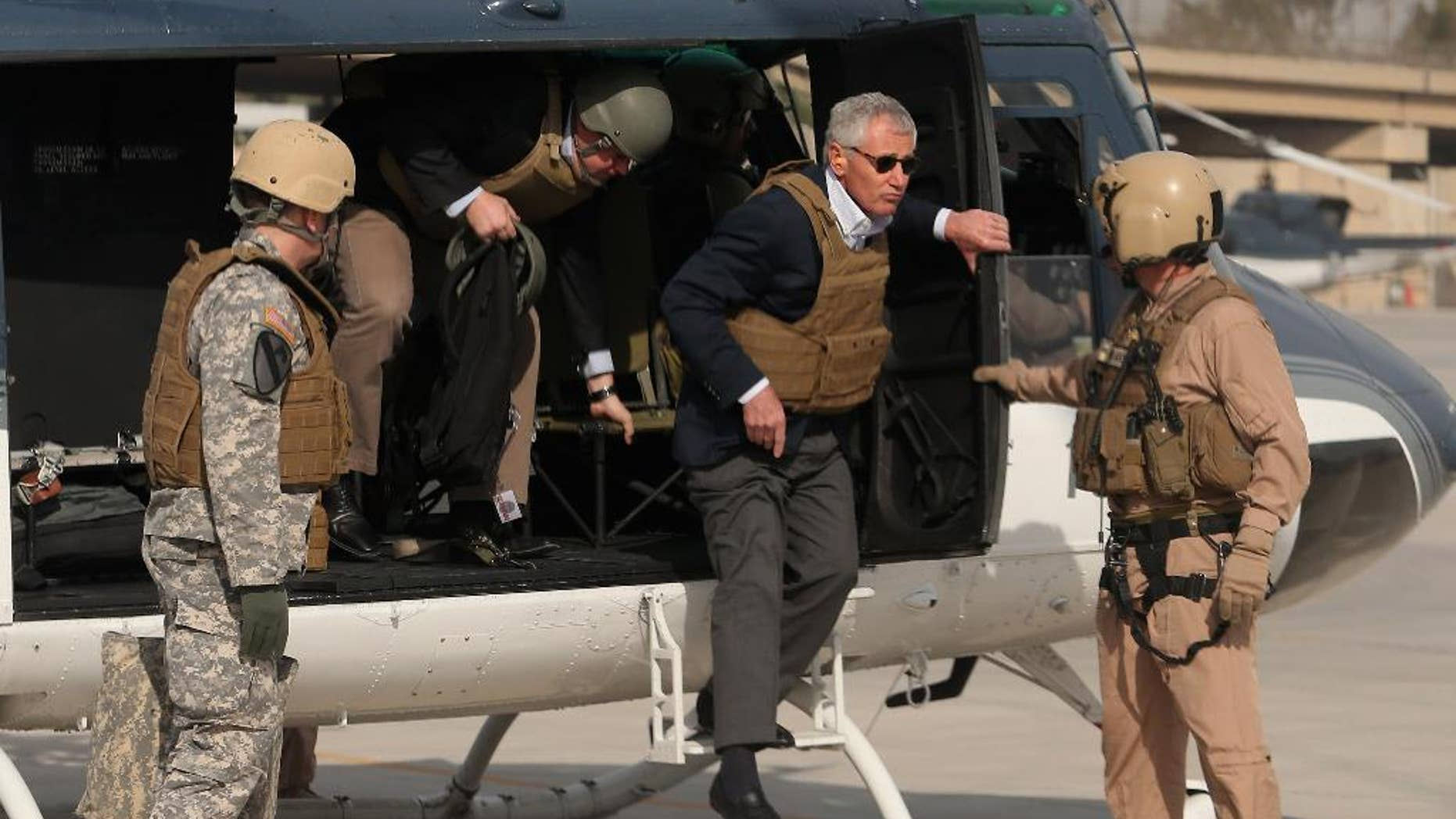 Defense Secretary Chuck Hagel, wearing body armor, steps off a helicopter in Baghdad, Iraq, Tuesday, Dec. 9, 2014, for a visit with military officials and Prime Minister Haider al-Abadi.  (AP Photo/Mark Wilson, Pool)