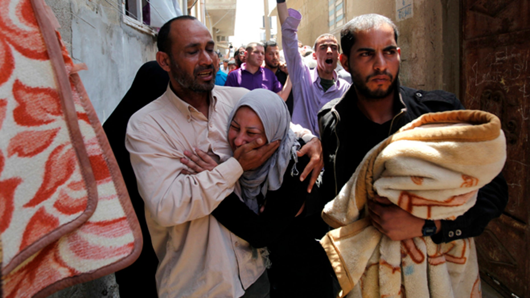 April 30, 2013: Palestinian relatives of Haitham Mishal, 29, react during his funeral in the Shati Refugee Camp in Gaza City. An Israeli aircraft attacked a motorcyclist in Gaza on Tuesday, killing the rider and wounding two other people in the first deadly airstrike in the Palestinian territory since a truce was reached with Palestinian militants last November. The Israeli military said the airstrike killed Haitham Mishal, whom it identified as a militant involved in the April 17 rocket attack on the southern Israeli resort town of Eilat.