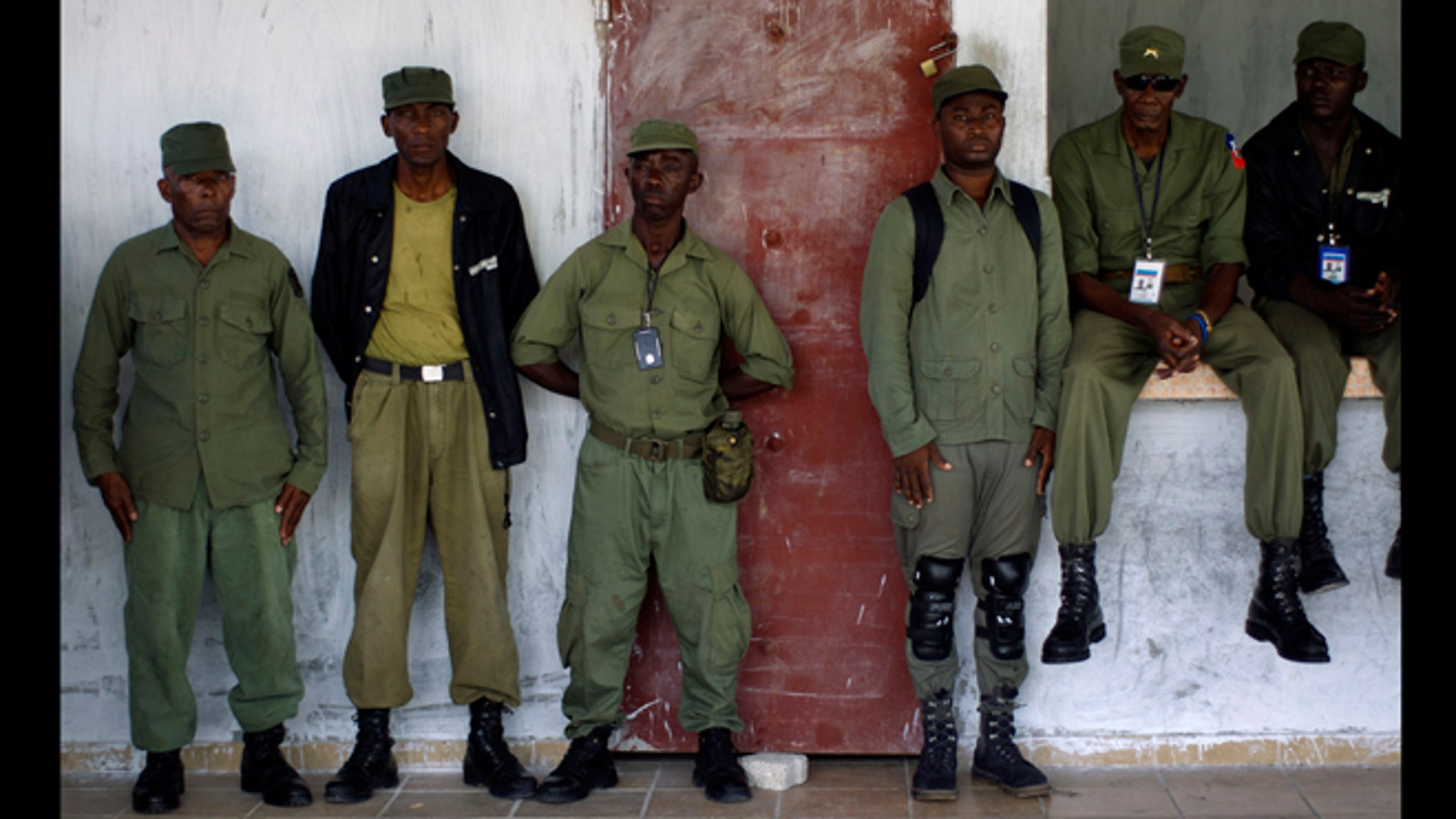 April 24, 2012: Members of the dissolved Haitian army and civilian volunteers listen to a military veteran during a press conference at an army barracks just outside Haiti's capital, Port-au-prince.