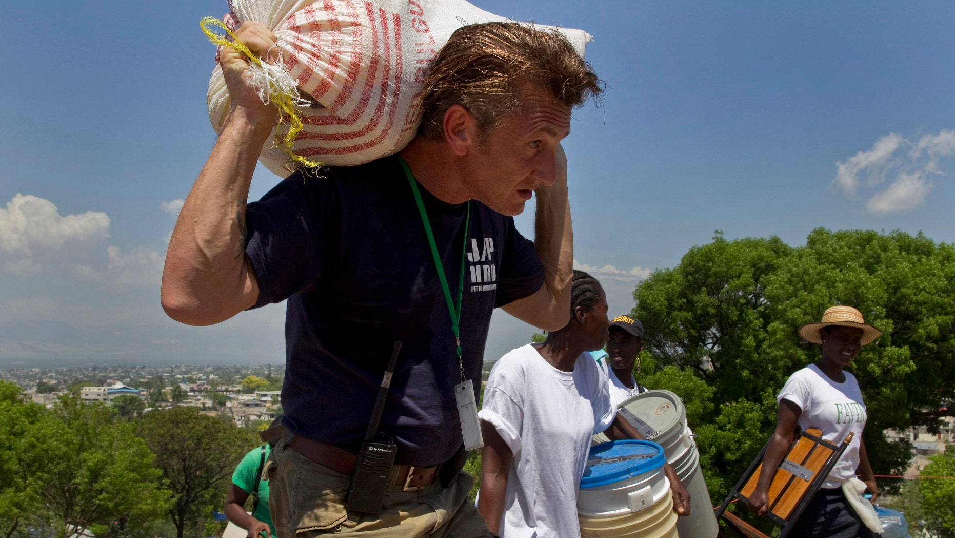 In this Saturday, April 10, 2010 file photo, U.S. actor Sean Penn carries the belongings of a person displaced by the earthquake as people are relocated from the Petionville Golf Club to a new camp, Corail-Cesselesse, in Port-au-Prince, Haiti. (AP Photo/Ramon Espinosa)