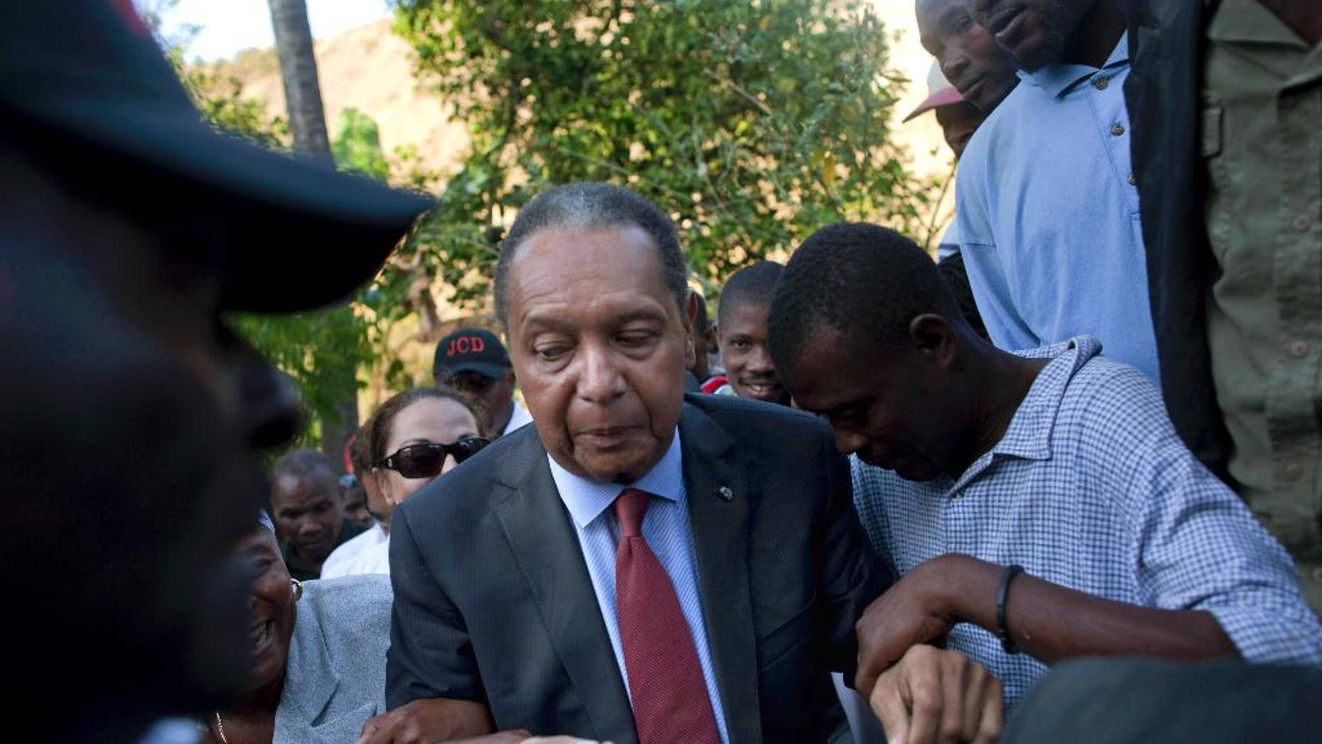 """FILE - In this Feb. 8, 2011 file photo, former Haitian dictator Jean-Claude """"Baby Doc"""" Duvalier's supporters help him negotiate an uneven path during a visit to his mother's hometown and grave site in Leogane, Haiti. Duvalier, the self-designated """"president-for-life"""" who died Oct. 4, 2014, from an apparent heart attack, will not get a formal state funeral, but have a """"simple, private,""""funeral arranged by friends and family in Haiti, attorney Reynolds Georges said in an interview. (AP Photo/Ramon Espinosa, File)"""