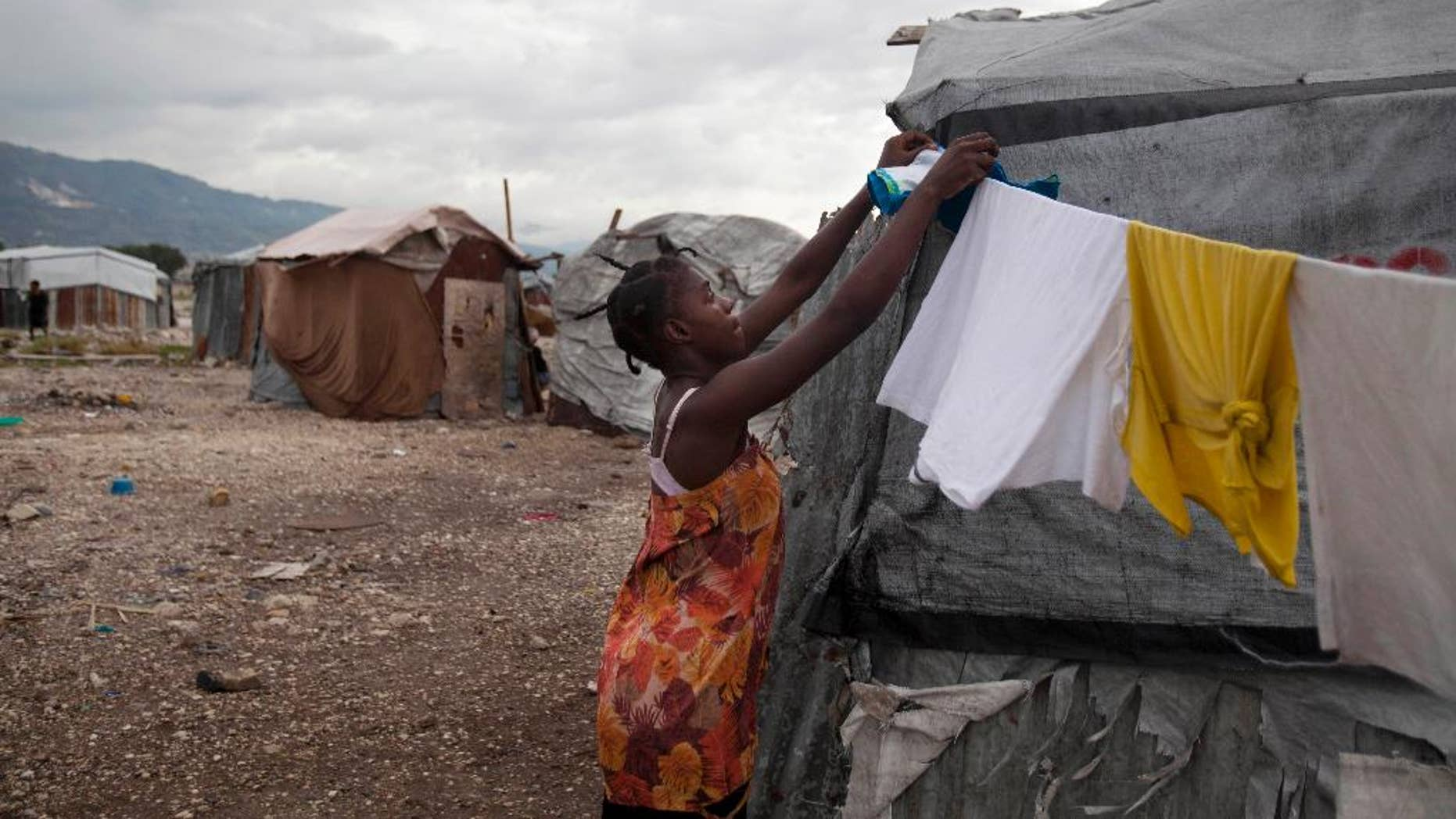 FILE - In this July 10, 2013 file photo, a woman fixes a clothes line next to her tent under cloudy skies caused by the nearby passing of Tropical Storm Chantal at the Jean-Marie Vincent camp for people displaced by the 2010 earthquake in Port-au-Prince, Haiti. A study released on Monday, April 7, 2014 finds that many of the camps are growing again, even as the overall population of quake refugees is falling. The study from the International Organization for Migration attributes the phenomenon mostly to people who have returned because they canít afford rents elsewhere. (AP Photo/Dieu Nalio Chery, File)