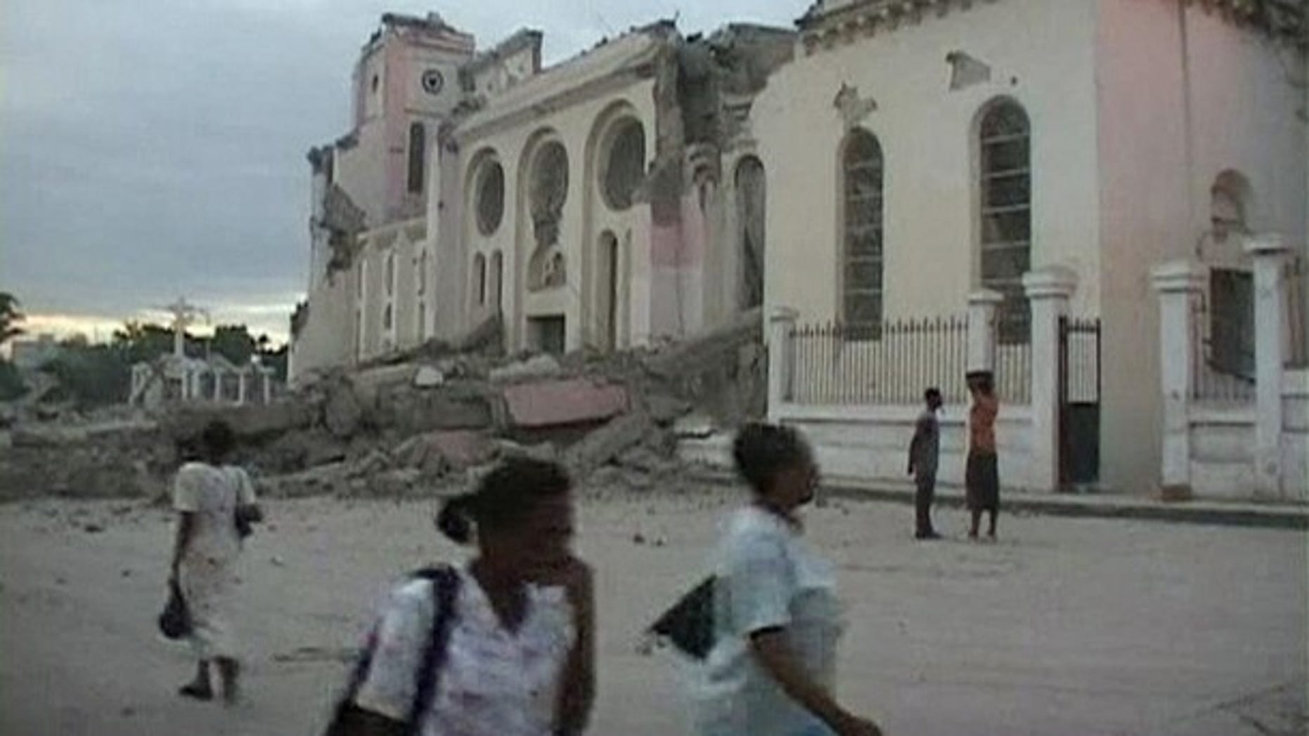 People walk near the ruins of a building, which was destroyed after a major earthquake struck near Port-au-Prince. The magnitude 7.0 quake toppled buildings and caused deaths and injuries.