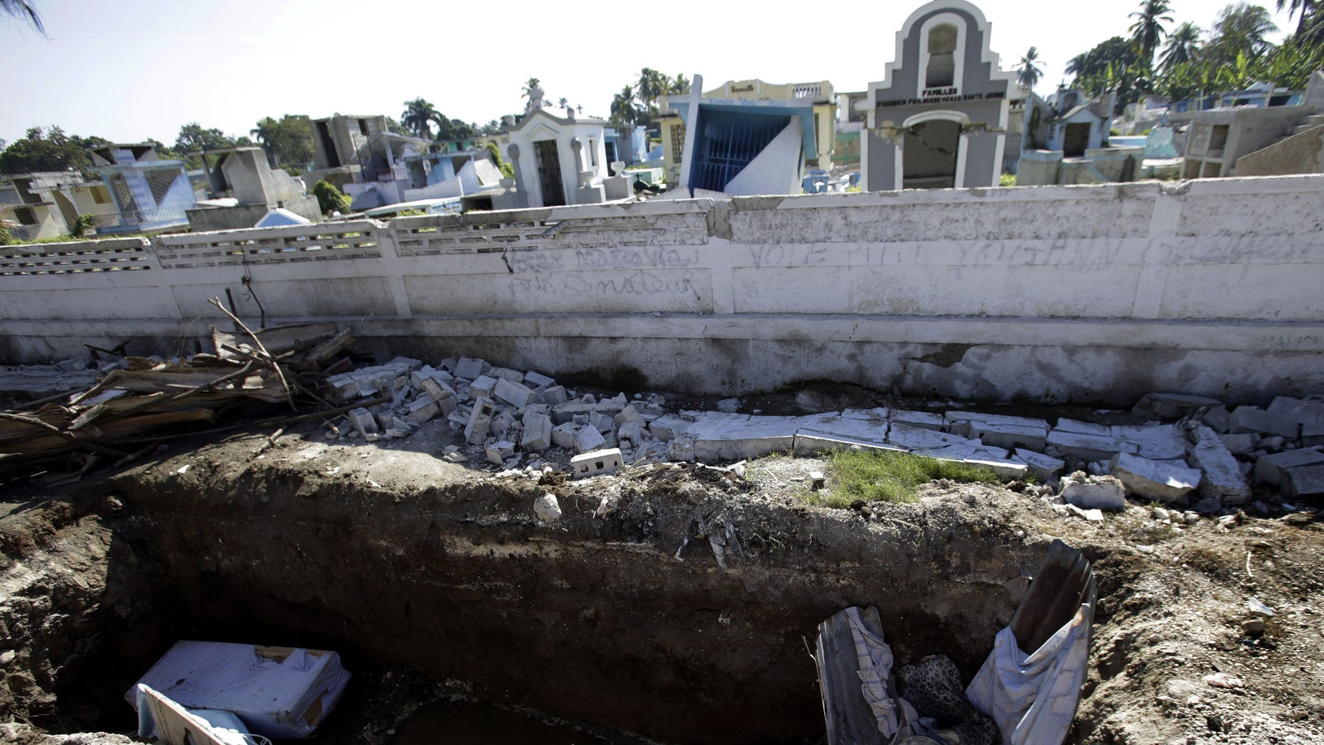Bodies lie in a mass grave outside a cemetery in Leogane, Haiti, Saturday, Jan. 16, 2010. While workers are burying in mass graves some of  the tens of thousand people killed in Tuesday's powerful earthquake, countless bodies remain unclaimed in the streets. (AP Photo/Lynne Sladky)