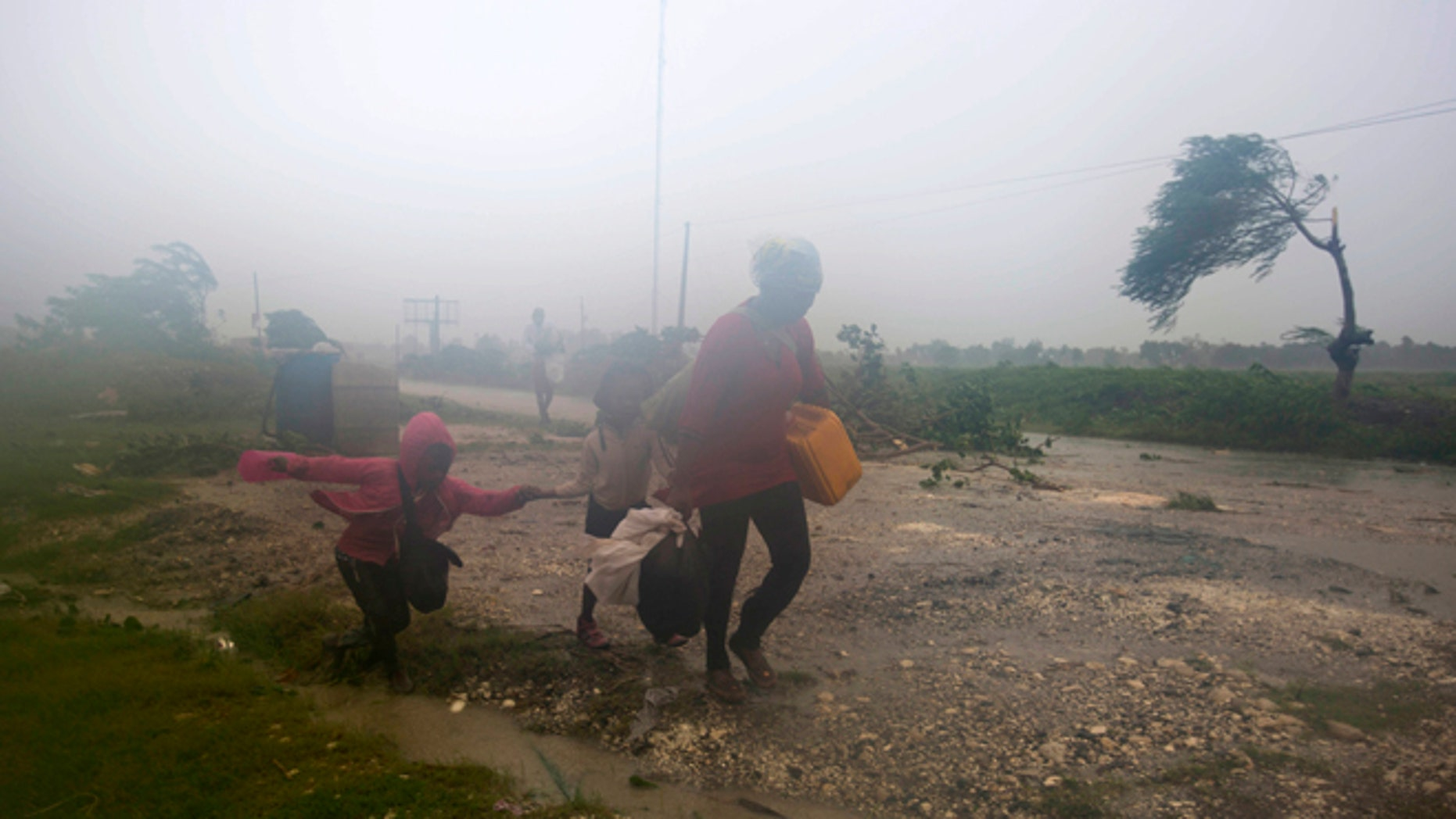 Residents head to a shelter in Leogane, Haiti, Tuesday, Oct. 4, 2016. Matthew slammed into Haiti's southwestern tip with howling, 145 mph winds Tuesday, tearing off roofs in the poor and largely rural area, uprooting trees and leaving rivers bloated and choked with debris.  (AP Photo/Dieu Nalio Chery)