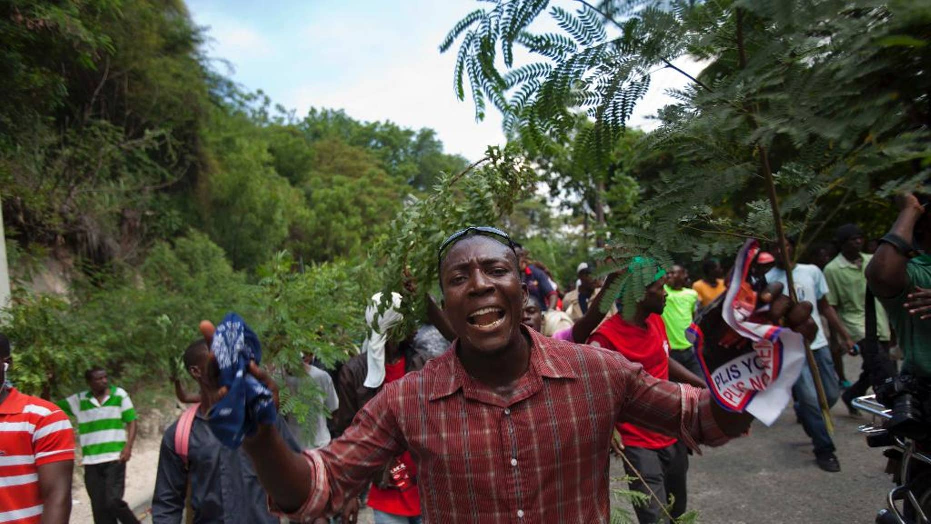 Demonstrators march during an anti-government protest in Port-au-Prince, Haiti, Sunday, Oct. 26, 2014. A few thousand protesters allied with Haiti's opposition marched through neighborhoods of the capital demanding the chance to vote in legislative and local elections that are three years late, among other grievances. (AP Photo/Dieu Nalio Chery)