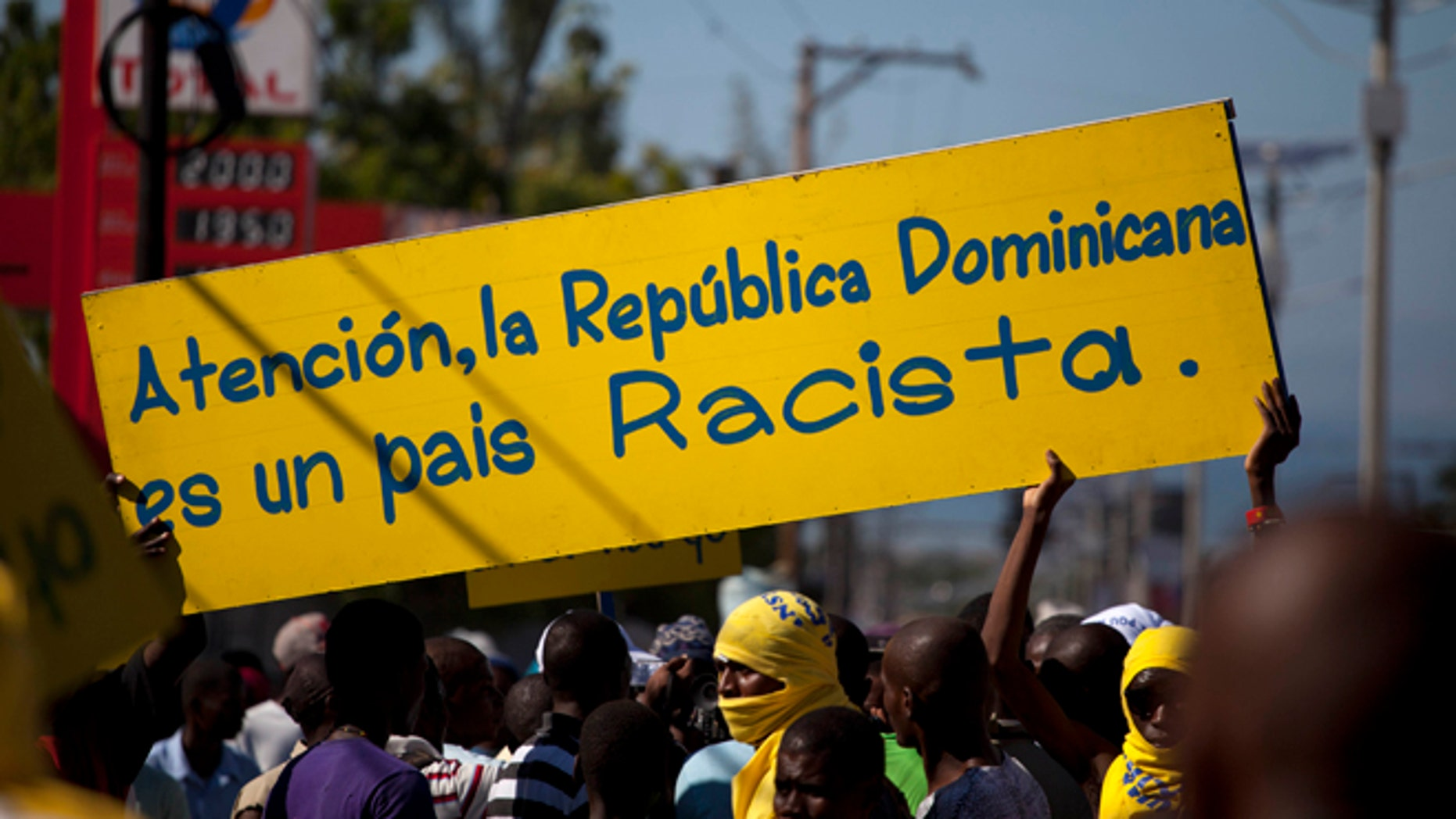 """Protesters hold a banner that reads in Spanish; """"Attention, the Dominican Republic is a racist country,"""" in Port-au-Prince, Haiti, Friday, Dec. 6, 2013. Hundreds of people gathered near the Dominica Embassy decrying a recent court decision in the Dominican Republic that could strip the citizenship of generations of people of Haitian descent living in the neighboring country. (AP Photo/Dieu Nalio Chery)"""
