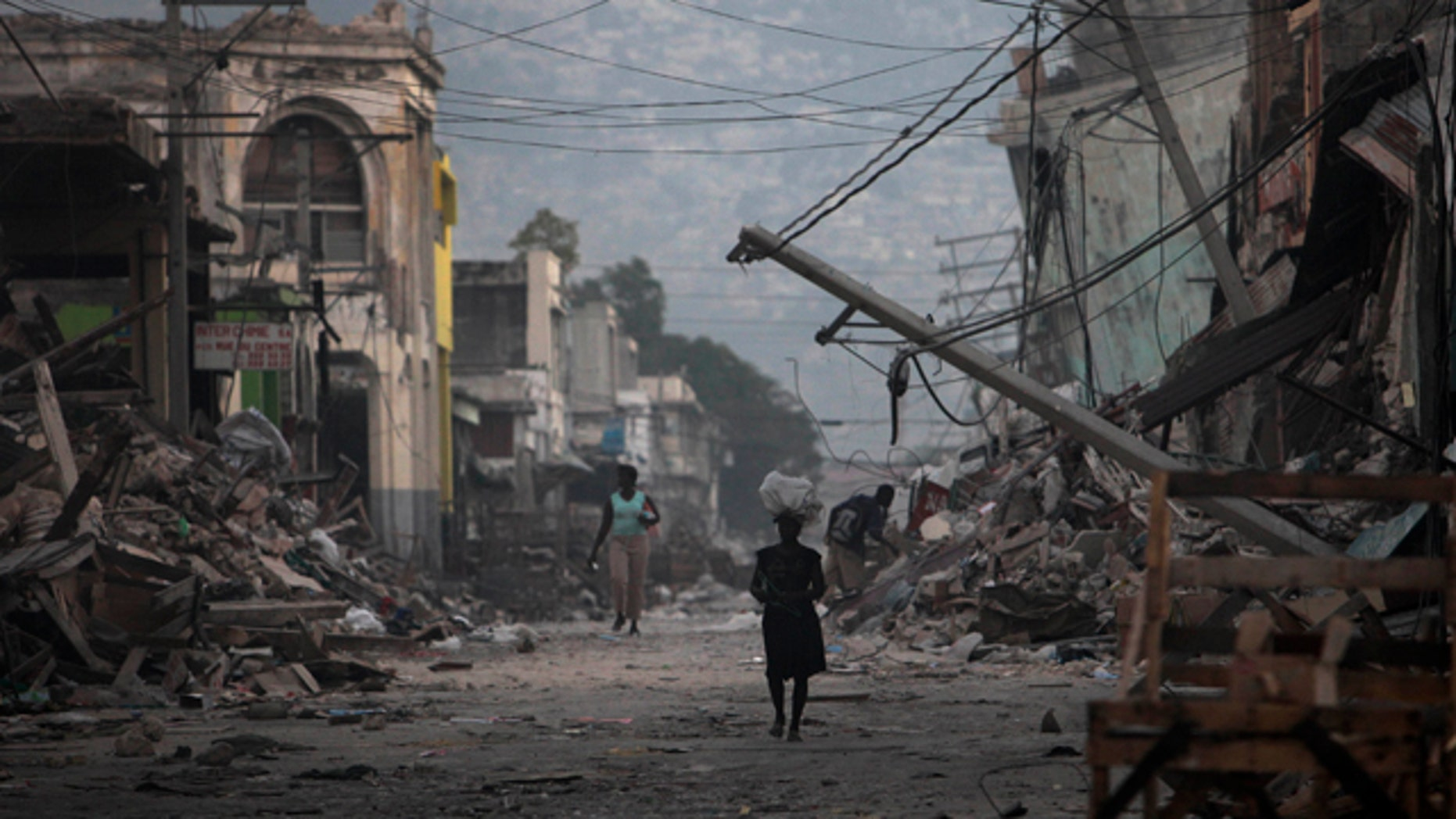 Jan. 20, 2010: A woman walks down a devastated street in Port-au-Prince, Haiti, a week after powerful 7.0-magnitude earthquake struck. Far fewer people died or were left homeless by last year's devastating earthquake than claimed by Haitian leaders, a report commissioned by the U.S. government has concluded.