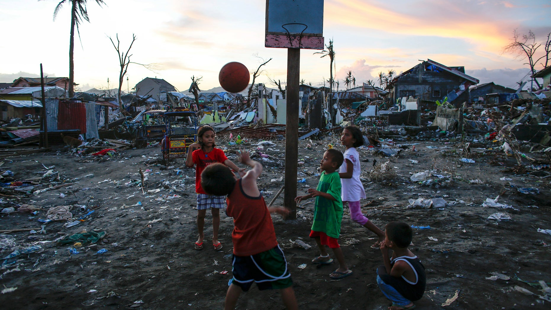 Children play basketball at an area devastated by Typhoon Haiyan in Tacloban city November 24, 2013. REUTERS/Athit Perawongmetha