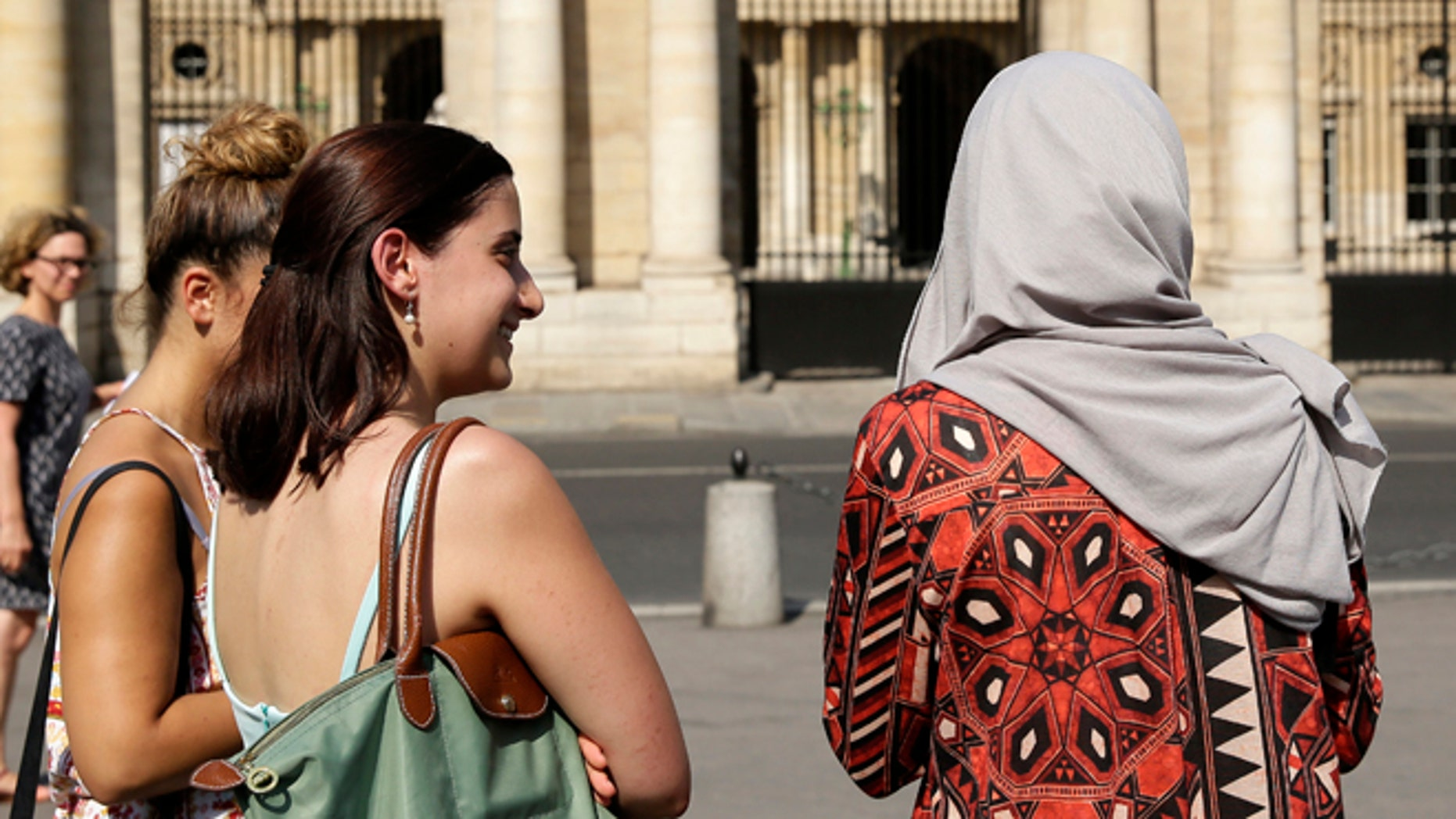 A woman wearing a Muslim headscarf, right, and who refused to be identified, stands outside the Conseil d'Etat, France's top administrative court, in Paris, Friday, Aug. 26, 2016. The court has overturned a town burkini ban amid shock and anger worldwide after some Muslim women were ordered to remove body-concealing garments on French Riviera beaches. (AP Photo/Thomas Padilla)