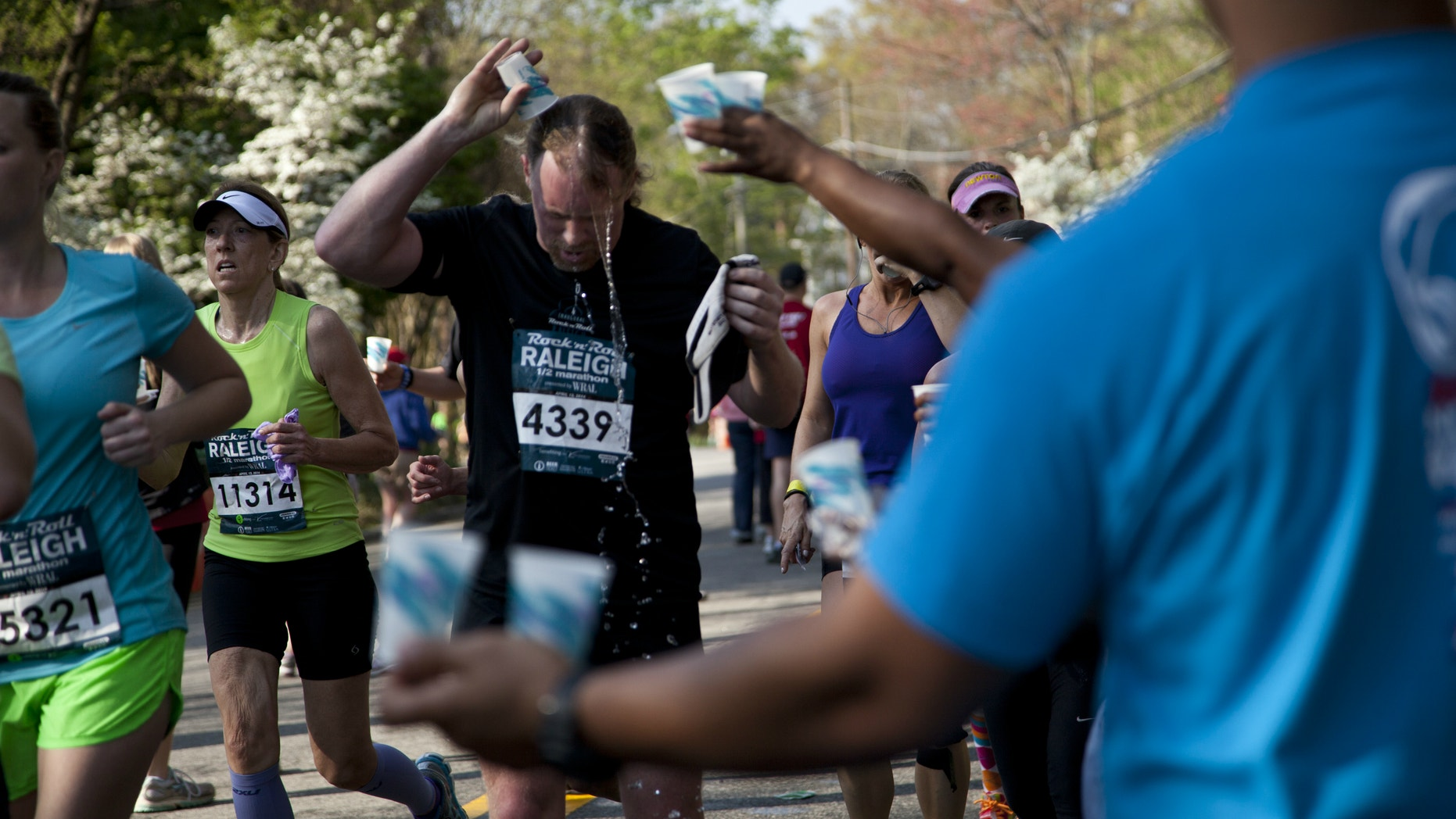 Fred Henninger Jr. pours water over his head at the mile 12 water station in Raleigh, NC during the Raleigh Rock 'n' Roll Marathon & Half Marathon, Sunday, April 13, 2014. Authorities say two runners have died near the finish line of the half marathon.