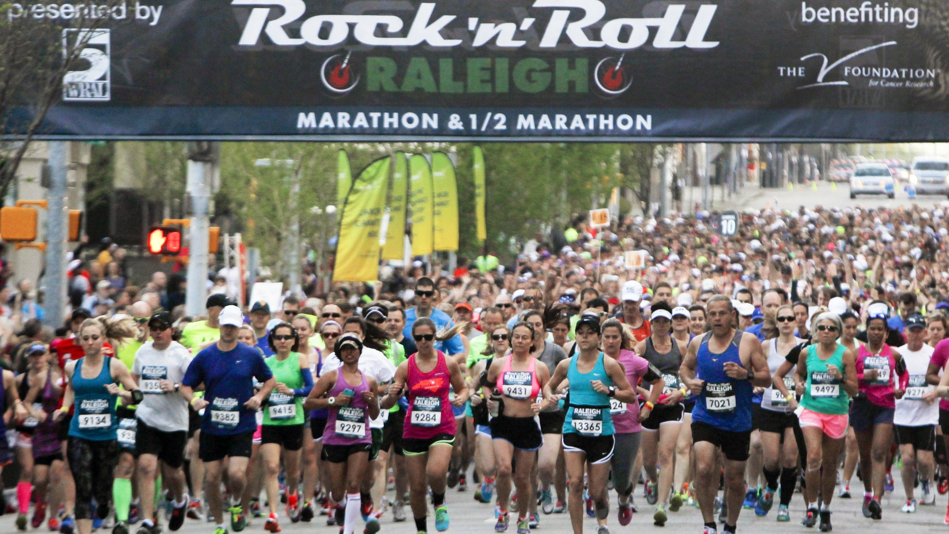 Runners head down Salisbury Street in Raleigh, N.C. during the Raleigh Rock 'n' Roll Marathon & Half Marathon, Sunday, April 13, 2014. Authorities say two runners died near the finish line of the half marathon.