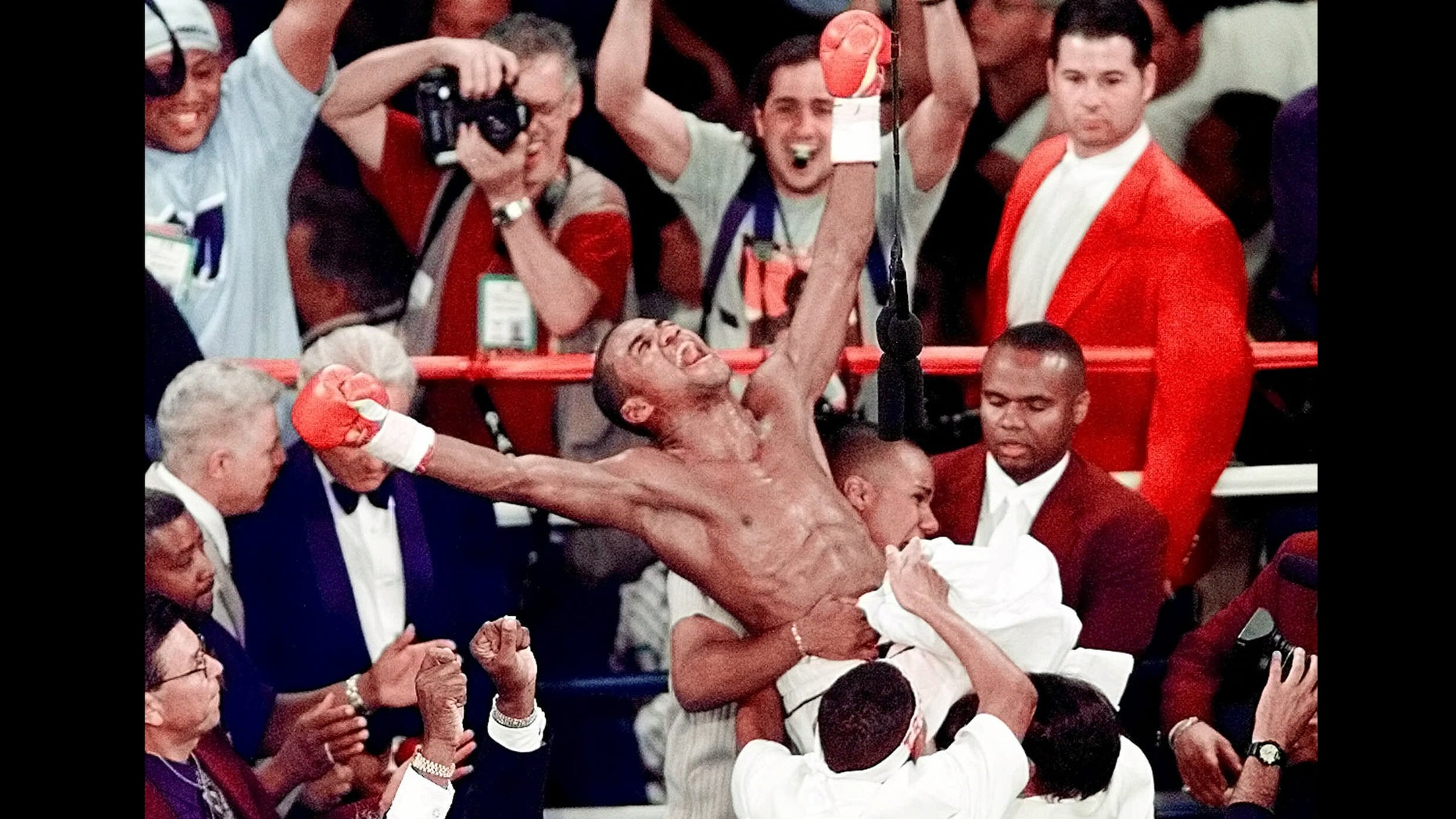 FILE - In this Sept. 18, 1999 file photo, Felix Trinidad is held up by his corner in after defeating Oscar De La Hoya by way of decision after 12 rounds, to win the WBC/IBF Welterweight Championship at the Mandalay Bay Events Center in Las Vegas. De La Hoya, Trinidad and Joe Calzaghe head the class of 2014 to be inducted into the International Boxing Hall of Fame. (AP Photo/Laura Rauch, File)