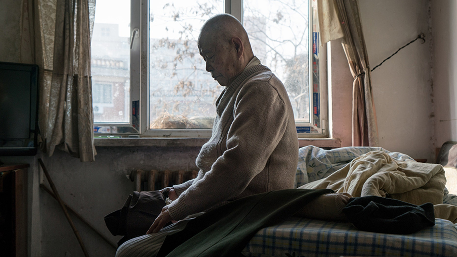 TIANJIN, CHINA - JANUARY 19: Han Zicheng, 85, sits in bed to take off his pants, revealing the wool pants inside that he usually wears at home. (Photo by Yan Cong for The Washington Post via Getty Images)