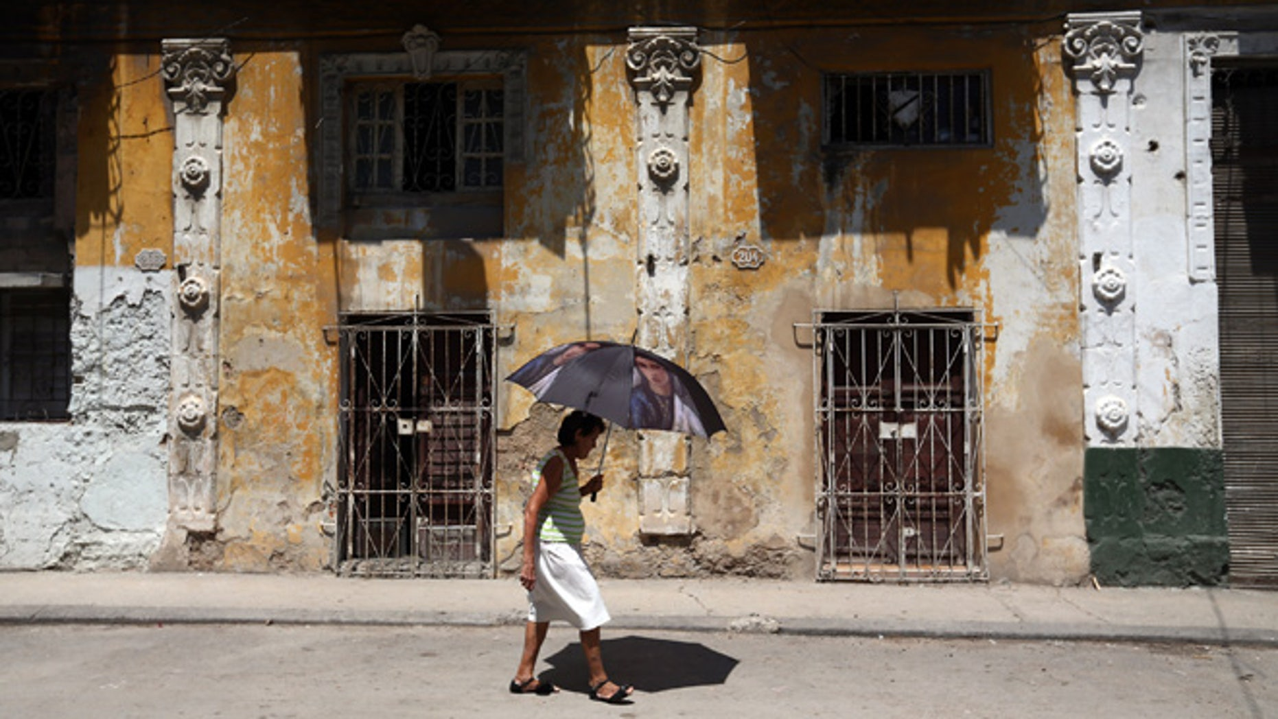 HAVANA, CUBA - SEPTEMBER 18: A woman shelters from the heat under an umbrella as she walks along a street on September 18, 2015 in Havana, Cuba. Pope Francis is due to make a three day visit to Cuba from September 19 where he will meet President Raul Castro and hold Mass in Revolution Square before travelling to Holguin, Santiago de Cuba, El Cobre and onwards to the United States. (Photo by Carl Court/Getty Images)