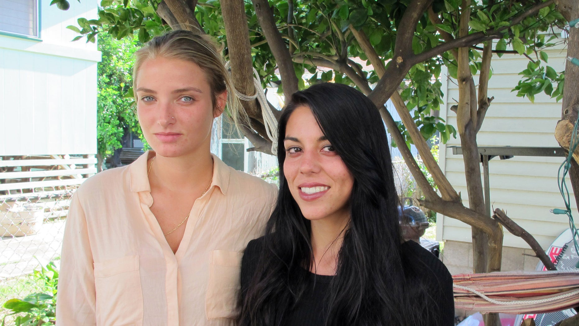 File-This Oct. 28, 2015, file photo shows Courtney Wilson, left, and Taylor Guerrero posing for a photo in Honolulu.  Honolulu will pay $80,000 to settle a lesbian couple's lawsuit alleging a city's police officer wrongfully arrested them after seeing them kissing in a grocery store while on vacation. The settlement was announced Friday, May 20, 2016, in federal court in Honolulu. It's still subject to City Council approval. Wilson and  Guerrero were visiting Hawaii form Los Angeles last year when they say they were harassed and arrested because the officer didn't like their public displays of affection in a Foodland store on Oahu's North Shore. (AP Photo/Jennifer Sinco Kelleher, File)