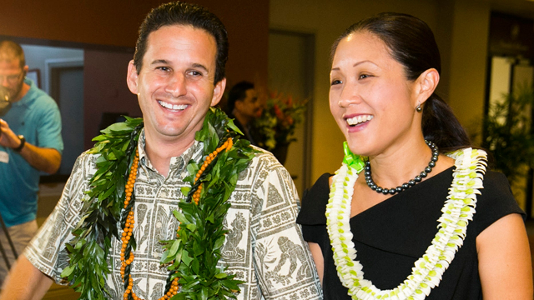 August 10, 2014: US Sen. Brian Schatz, left, and Linda Kwok Schatz attend the Democratic Unity Breakfast in Honolulu.  The breakfast is traditionally held after Hawaii elections and is attended by both winners as well as losers.  (AP Photo/Marco Garcia)