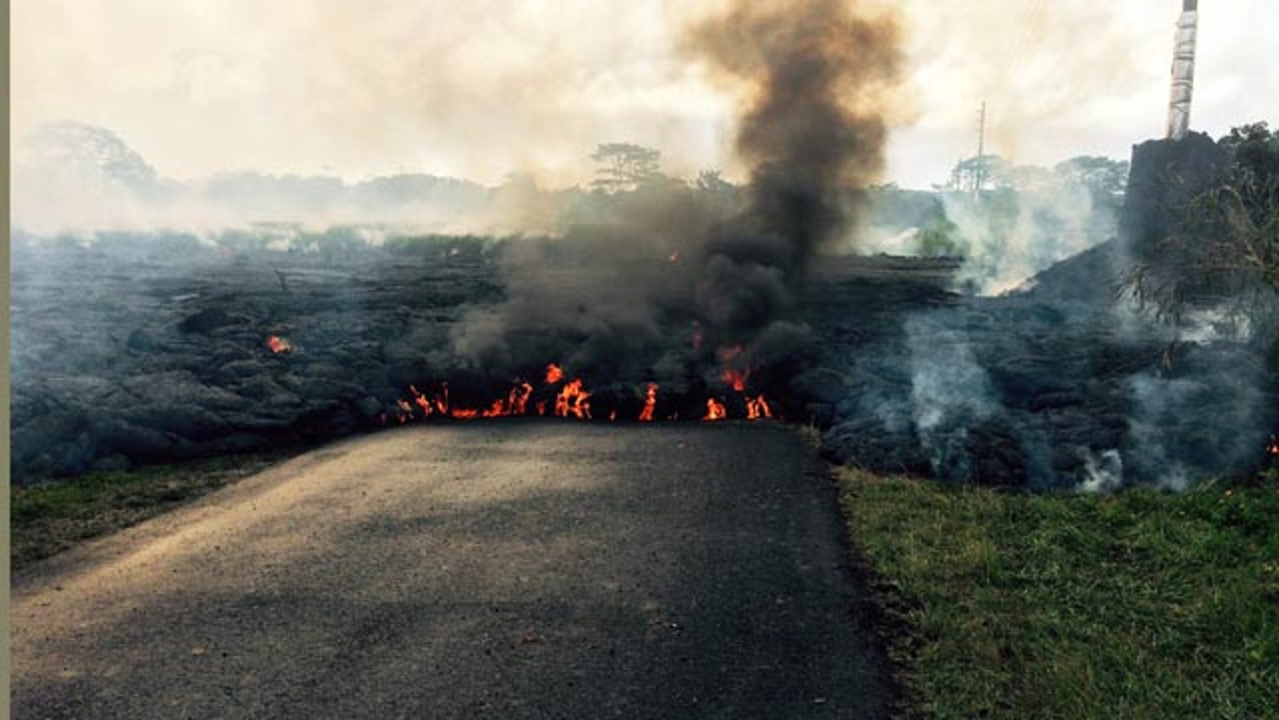 October 24, 2014: In this photo from the U.S. Geological Survey, the lava flow from Kilauea Volcano that began June 27 is seen as it crossed Apa'a Street near Cemetery Road near the town of Pahoa on the Big Island of Hawaii. (AP/U.S. Geological Survey)