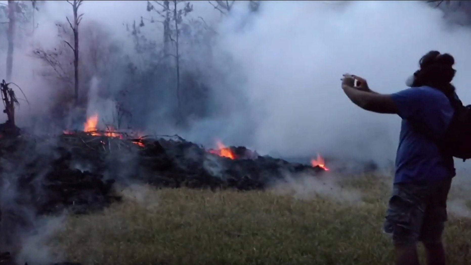 A man in a gas mask takes pictures of a lava fissure at Leilani Estates, Hawaii, this week.