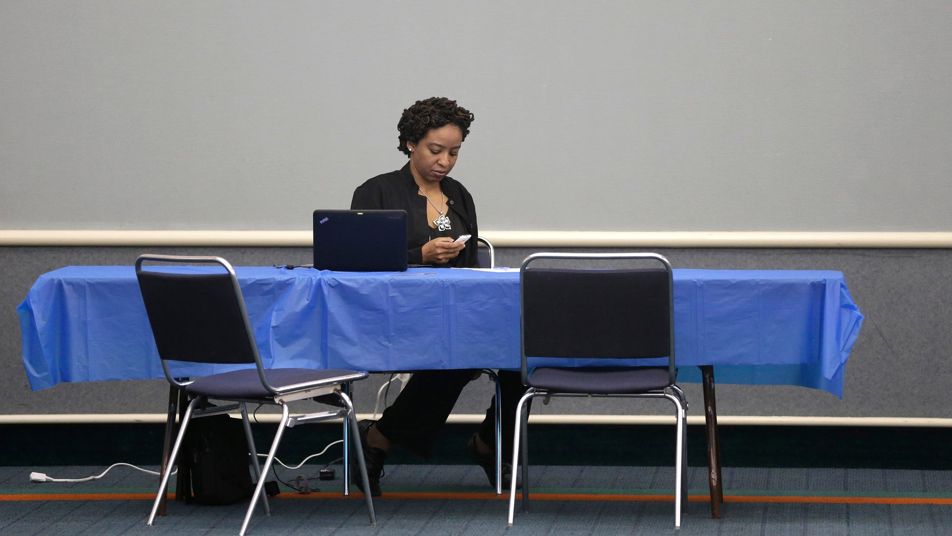 Health care assister Charolyn Mosley looks at her cell phone as she waits to help anyone looking to shop the  federal marketplace for health insurance at a convention center in Texas City, Texas, Saturday, March 1, 2014. Though organizers had recruited assisters to handle as many as 400 people in navigating the federal insurance marketplace, only a handful had come by in the first hours of operations.