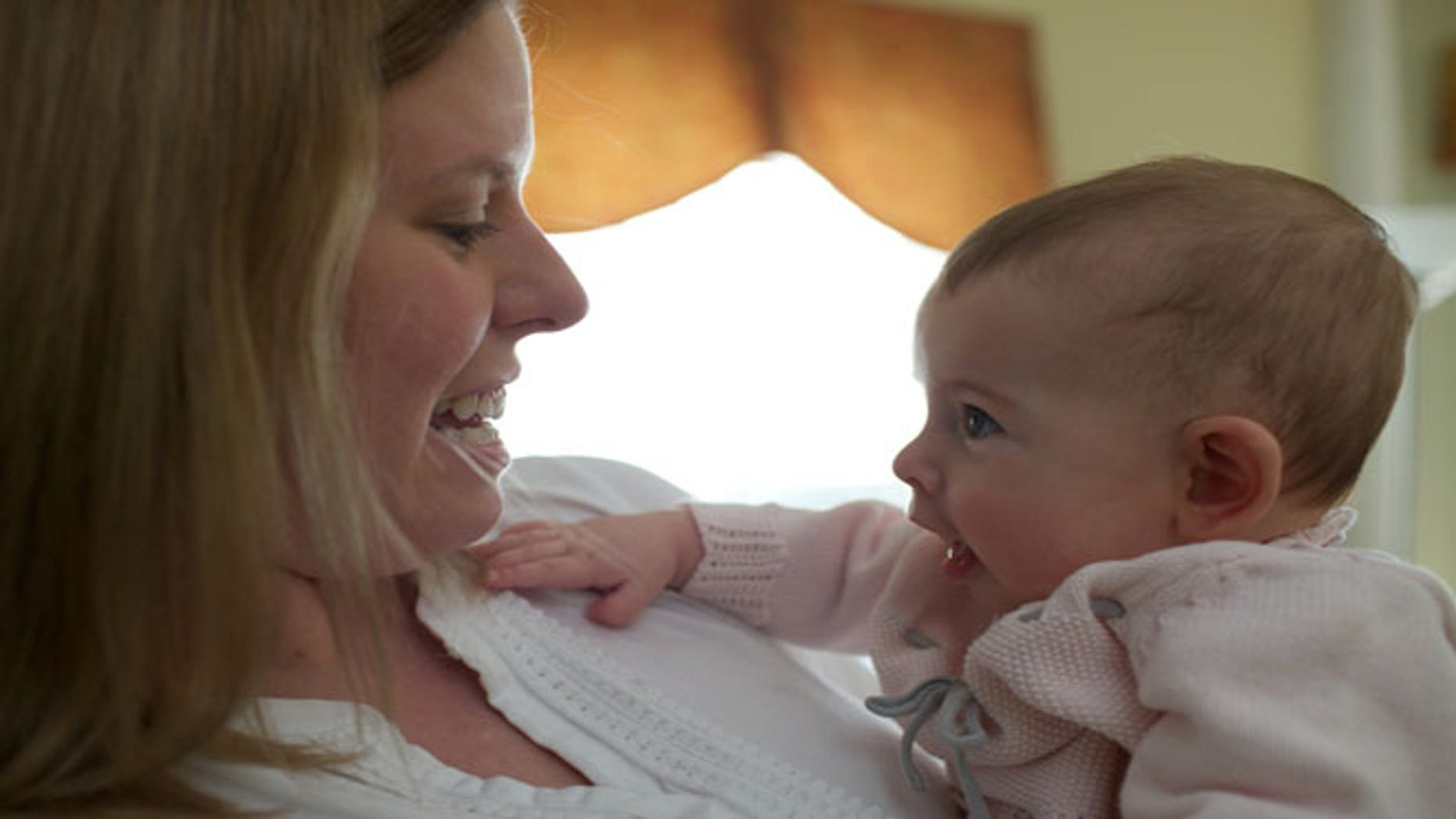 In this photo taken Sept. 24, 2013, Holly Sloan interacts with her baby Amelia at their home in Warrenton, Va. Ameliaâs family enrolled in a study that is deciding the DNA of babies, as researchers explore whether gene-mapping one day should become a part of newborn care.