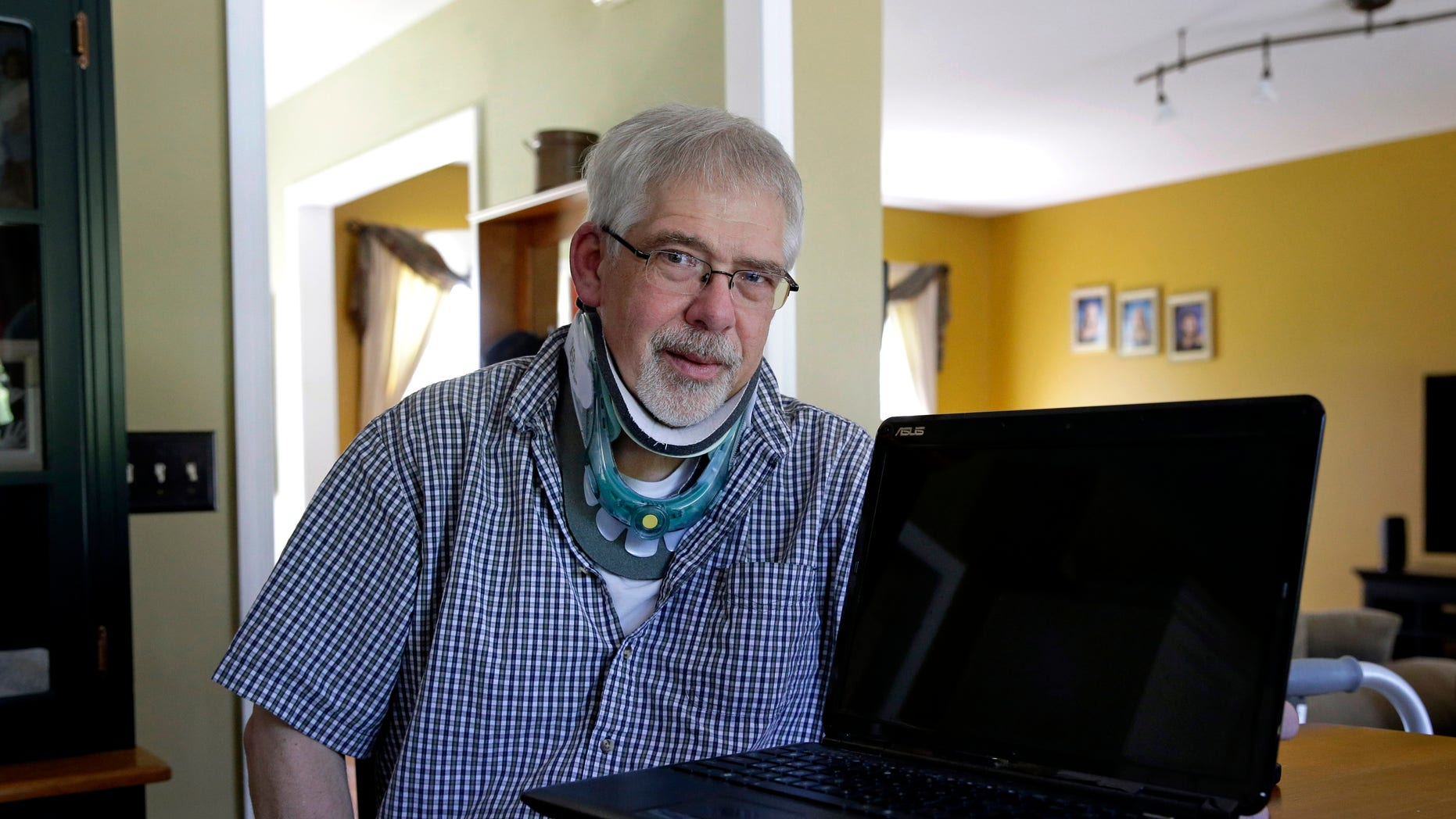 Mark Matulaitis poses with the laptop that he uses for virtual house calls with his neurologist in his home in Salisbury, Md. Matulaitis has had Parkinson's disease since 2011 and sees a neurologist at the University of Rochester via his laptop and special Skype-like software.  (AP Photo/Patrick Semansky)