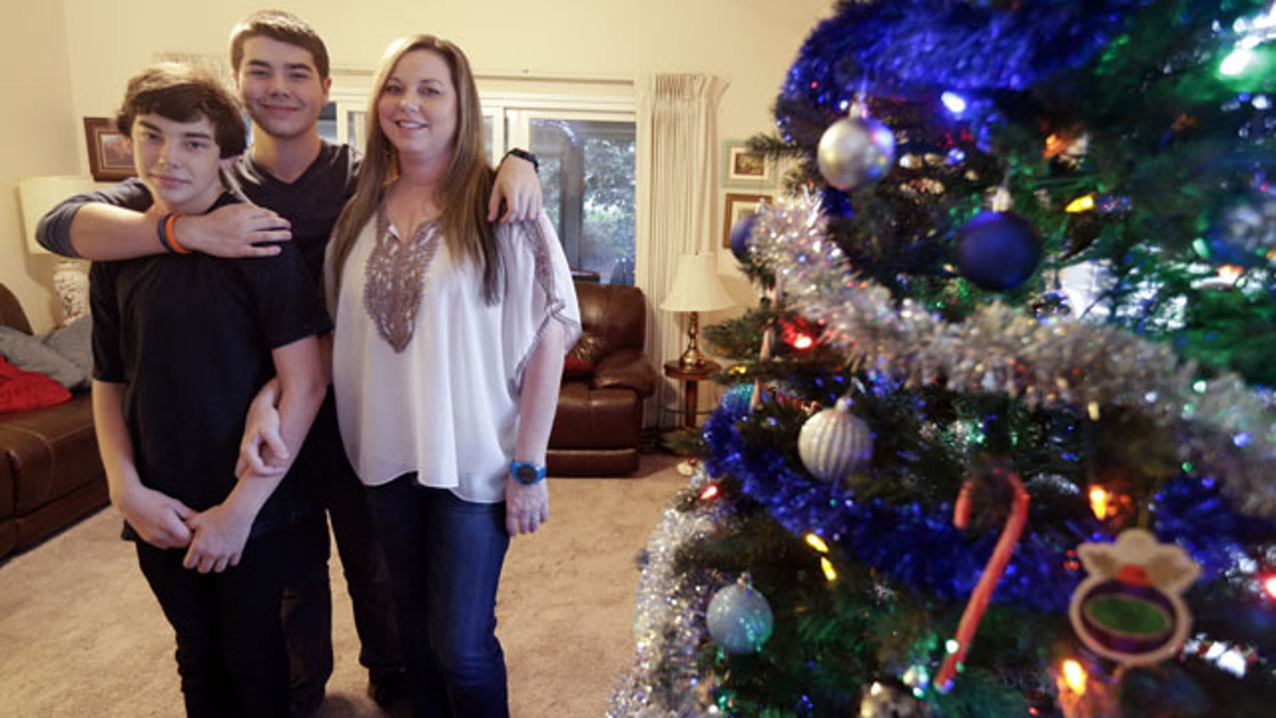 December 17, 2013: Matthew Kremis, center, poses for a picture with his brother Trevin Kremis, left, and their mother, Deanna Kremis, in their home in San Marcos, Calif. All three have received heart transplants, after suffering from an inherited heart condition. (AP Photo/Gregory Bull)