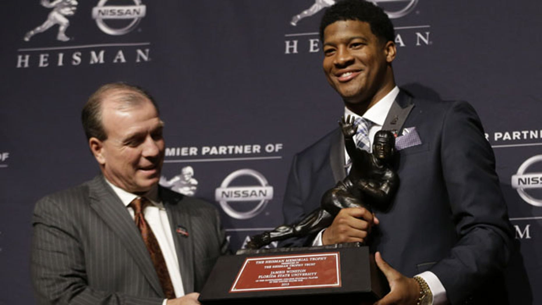 December 14, 2013: Florida State quarterback Jameis Winston, right, stands with FSU coach Jimbo Fisher while holding the Heisman Trophy after winning the award in New York. (AP Photo/Julio Cortez)