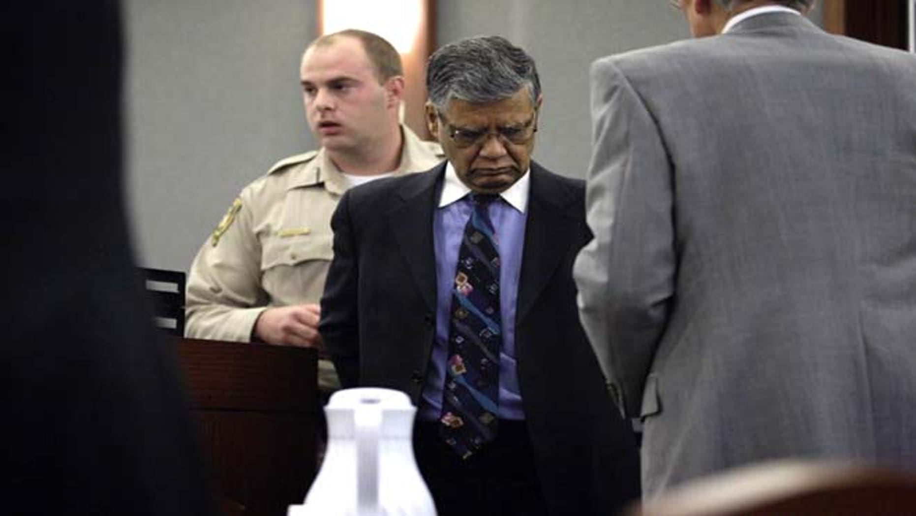 July 1, 2013: Former doctor and endoscopy clinic owner Dipak Desai right, is taken into custody by Clark County marshals at the Regional Justice Center in Las Vegas Monday, July 1, 2013 after a jury found him guilty. Nevada state court jury found Desai guilty of all 27 criminal charges against him— including second-degree murder — in a 2007 hepatitis C outbreak that officials called one of the largest ever in the U.S. (AP Photo/Las Vegas Review-Journal, Jessica Ebelhar)