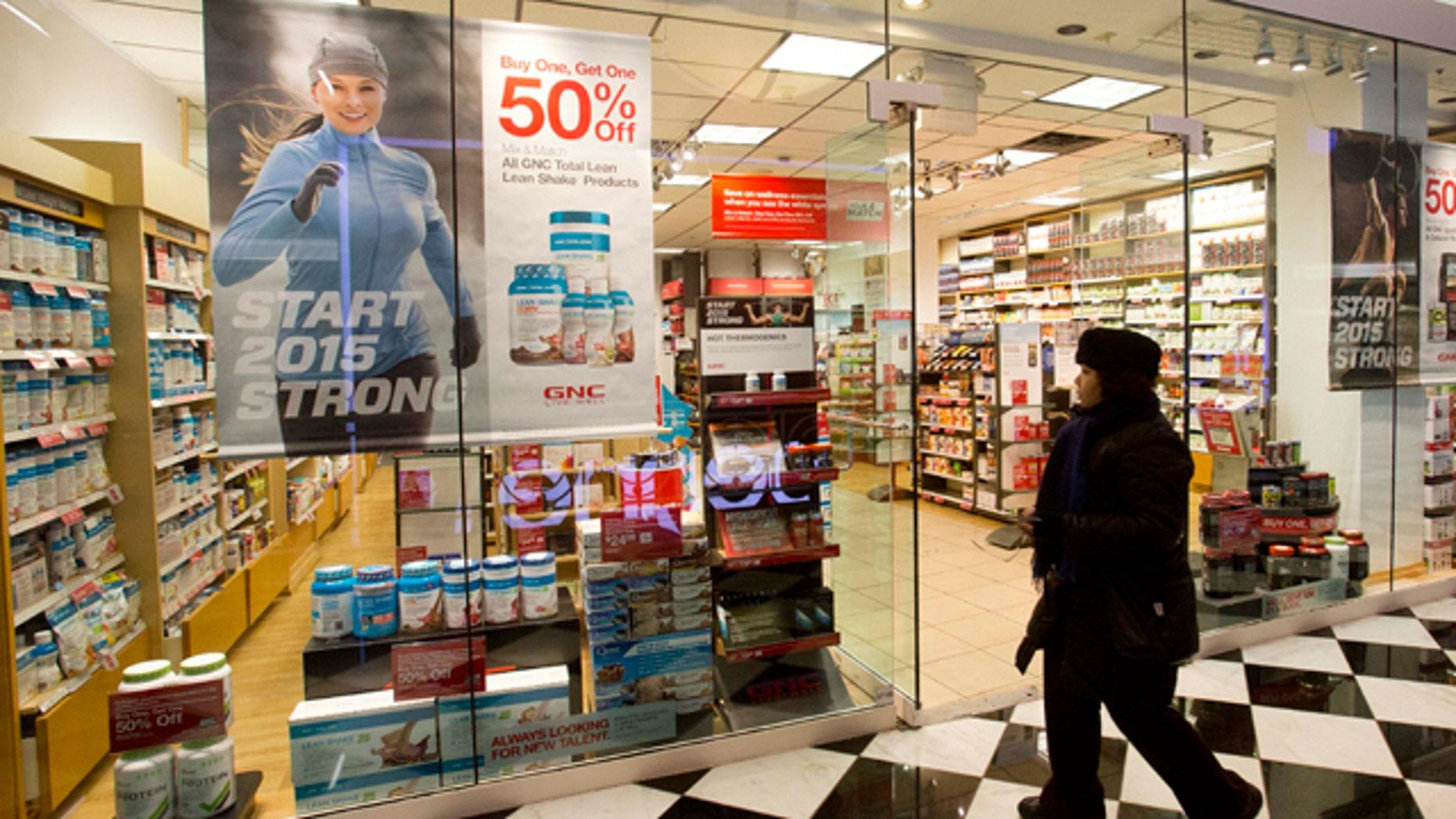 Feb. 3, 2015: A woman walks past a GNC store in New York. (AP Photo/Mark Lennihan)