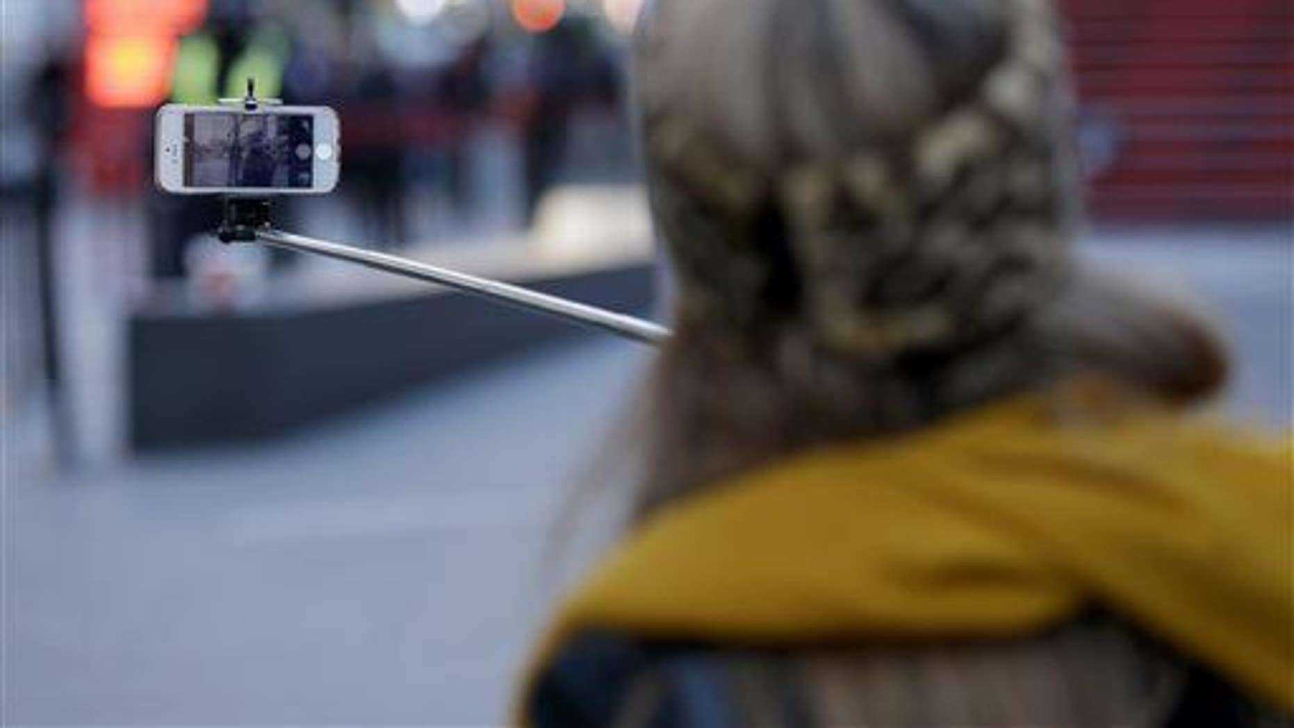 Sandy Johal uses a selfie stick to take a picture of herself in Times Square in New York, Jan. 8, 2015.