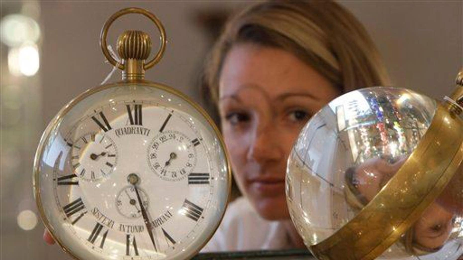 A Bonhams employee holds two Victorian glass and brass bull's-eye desktop clocks on view at Bonhams auction house in London, Monday, Sept. 28, 2009, in London.