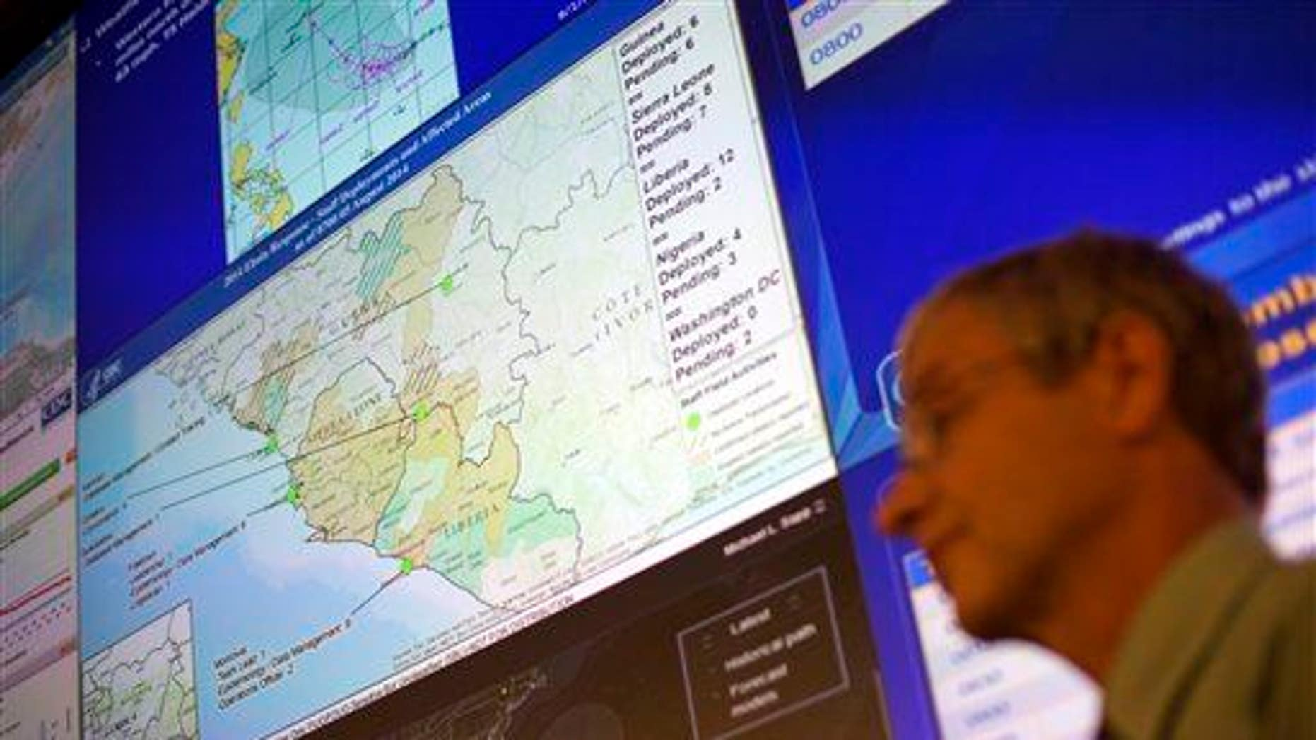 A CDC official stands under a map showing the agency's deployment of workers in West Africa at the agency's Emergency Operations Center, Tuesday, Aug. 5, 2014, in Atlanta.