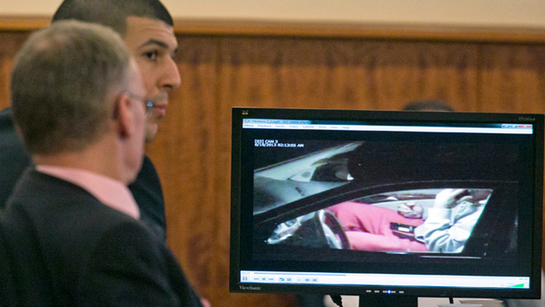 Aaron Hernandez, rear, and his attorney Charles Rankin watch surveillance video of Hernandez handling cell phones during his murder trial at the Bristol County Superior Court in Fall River, Mass. on Tuesday, Feb. 17, 2015. Hernandez is accused in the June 17, 2013, killing of Odin Lloyd, who was dating his fiancée's sister. (AP Photo/Dominick Reuter, Pool)