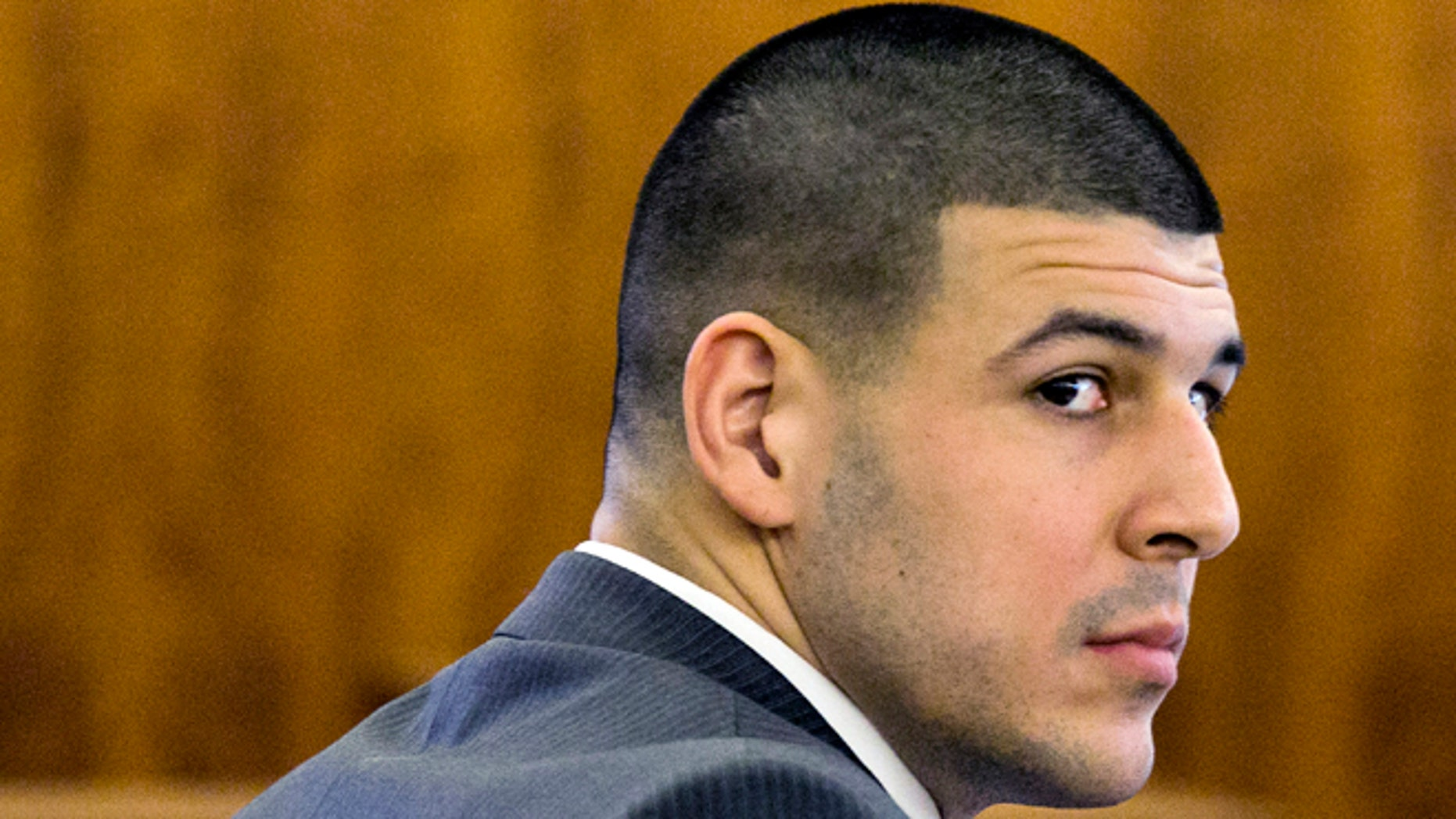 Former New England Patriots football player Aaron Hernandez looks at the prosecutor during his murder trial at Bristol County Superior Court Tuesday, March 3, 2015, in Fall River, Mass.  Hernandez is accused of the June 2013 killing of Odin Lloyd. (AP Photo/Dominick Reuter)