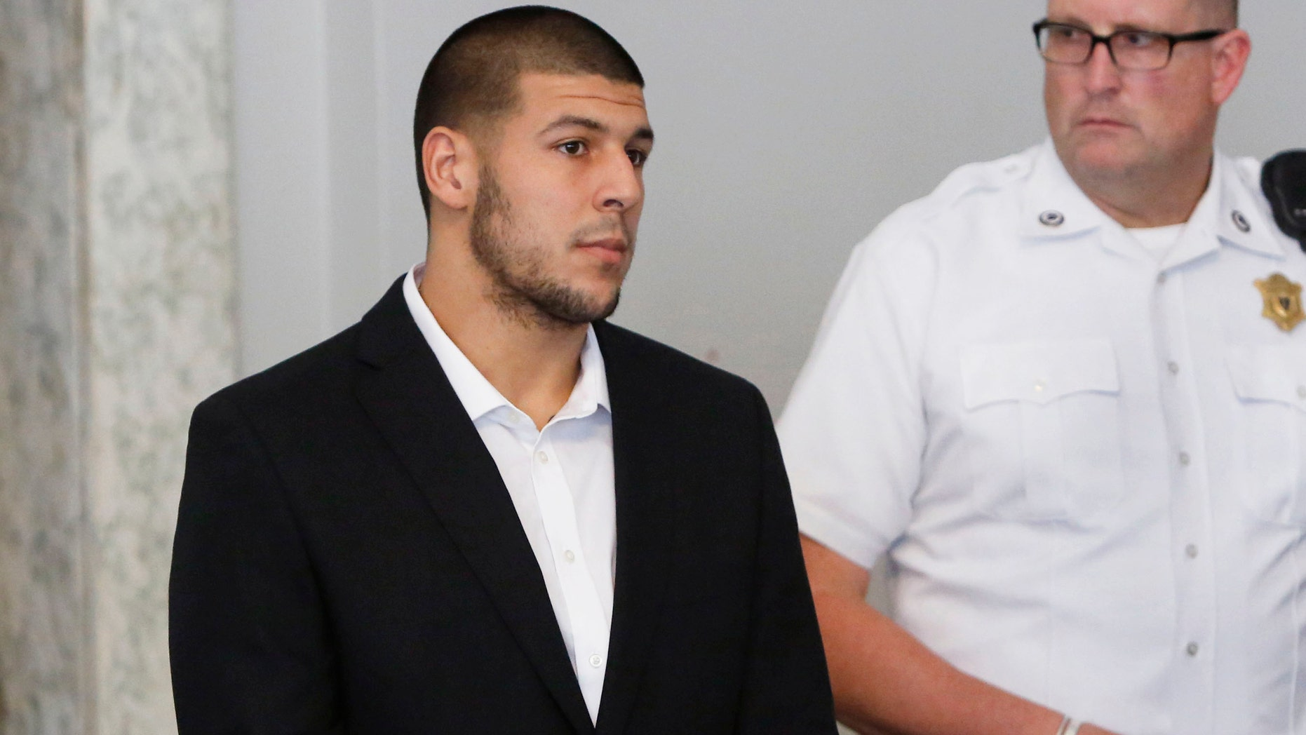 Former New England Patriots NFL football tight end Aaron Hernandez, left, appears at Attleboro District Court on Wednesday, July 24, 2013, in Attleboro, Mass.