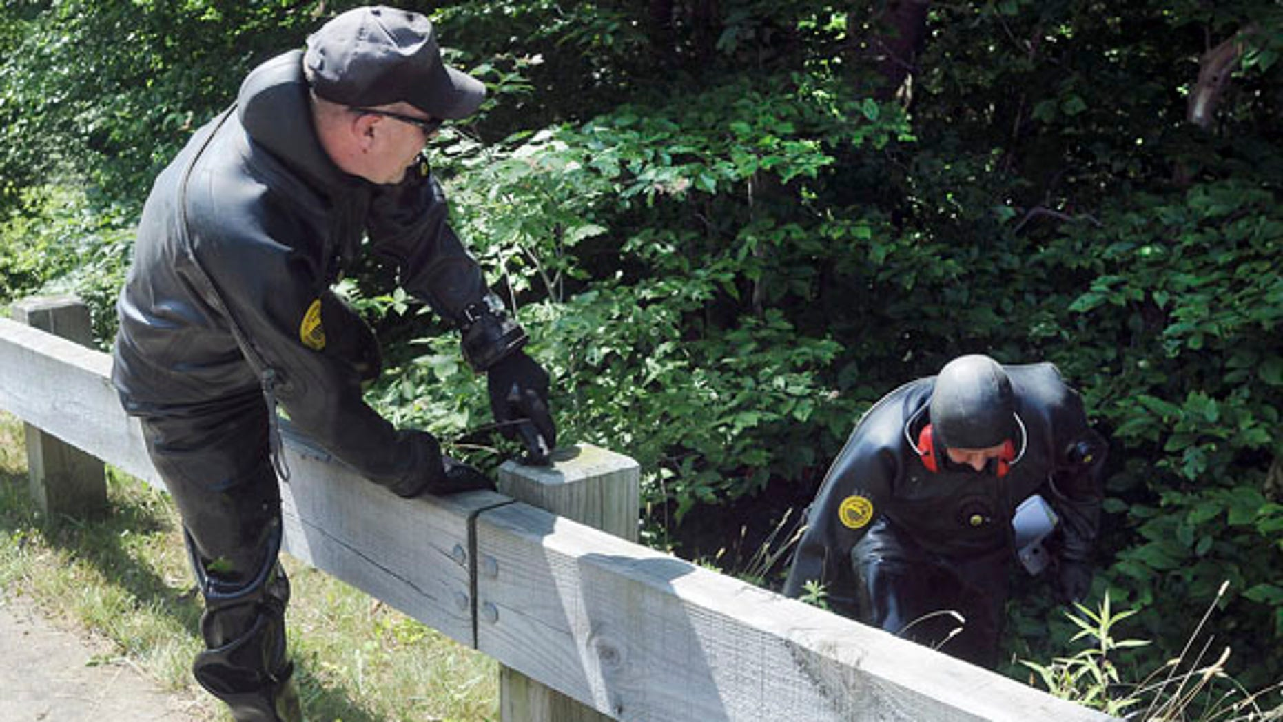 June 24, 2013: Law enforcement officers wearing wetsuits emerge from bushes during a search for evidence along a road near the home of New England Patriot's NFL football player Aaron Hernandez in North Attleborough, Mass.