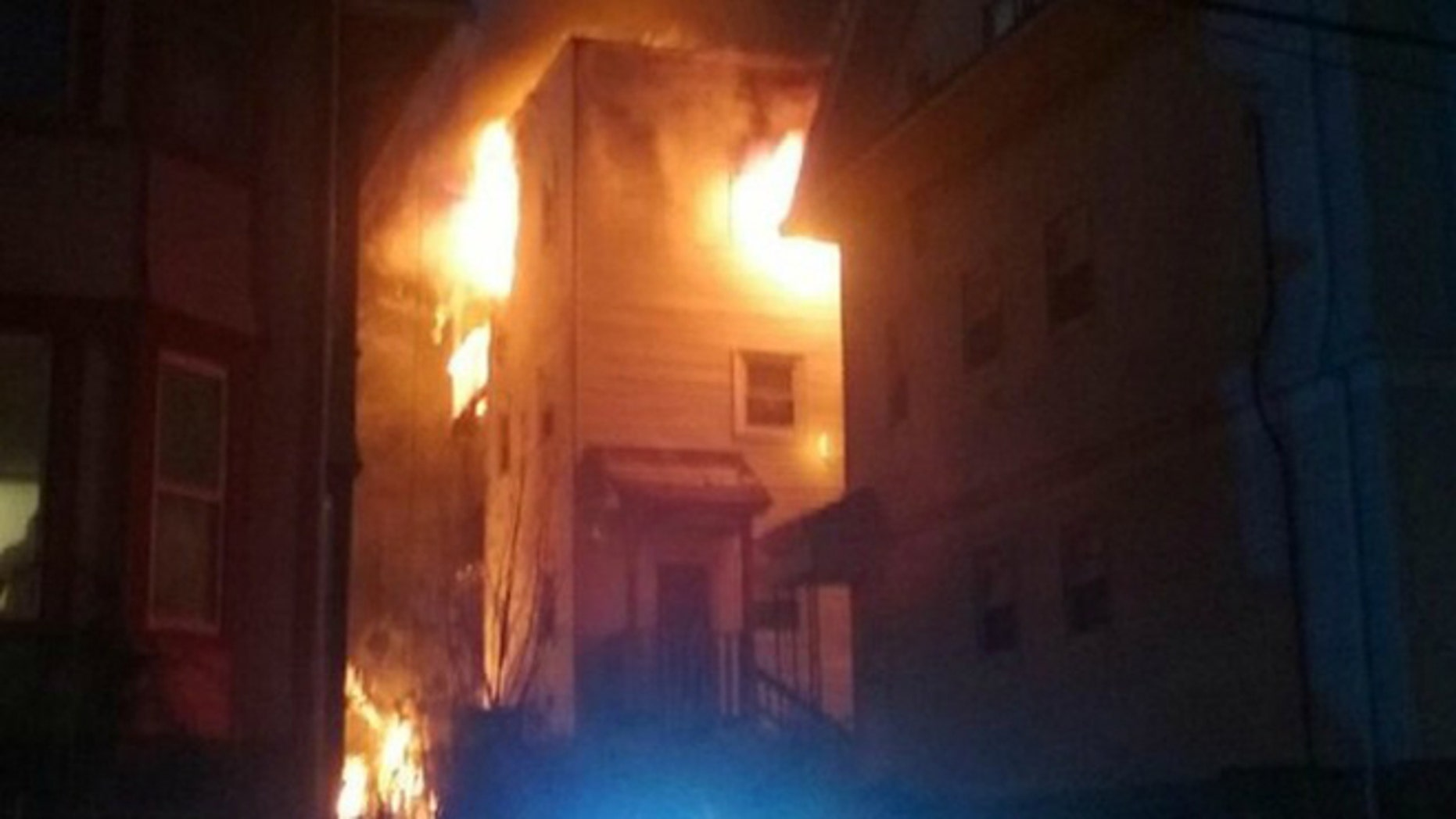 The burning townhouse in Dorchester where Officer Luis Lopez helped saved 18 residents. (Photo: MyFoxBoston)