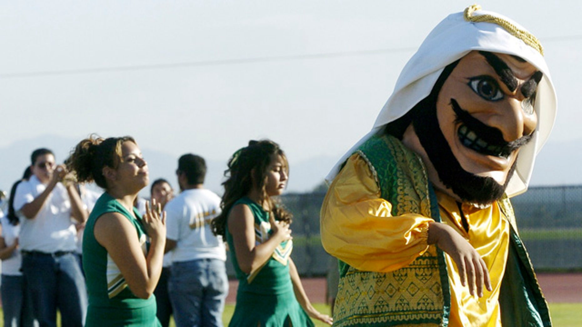FILE - In this Nov. 10, 2005, file photo, Coachella Valley High School's mascot, 'Arab,' dances to the band during a pep rally at the school in Thermal, Calif. The hook-nosed, snarling mascot who wears a head scarf did not appear at Coachella Valley High School's season opening football game Friday. (AP Photo/The Desert Sun, Marilyn Chung, File)