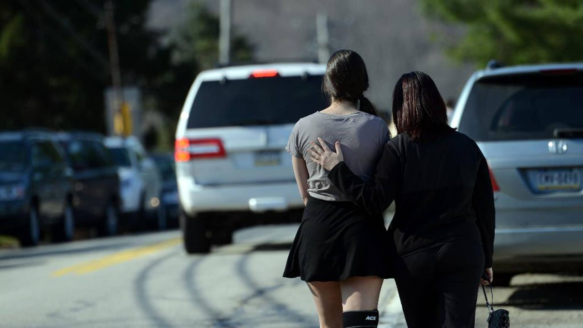 A parent consoles their child as the leave Franklin Regional High School after more than a dozen students were stabbed by a knife wielding suspect at the school on Wednesday, April 9, 2014, in Murrysville, Pa., near Pittsburgh. The suspect, a male student, was taken into custody and is being questioned. (AP Photo/Tribune Review, Sean Stipp)  PITTSBURGH OUT