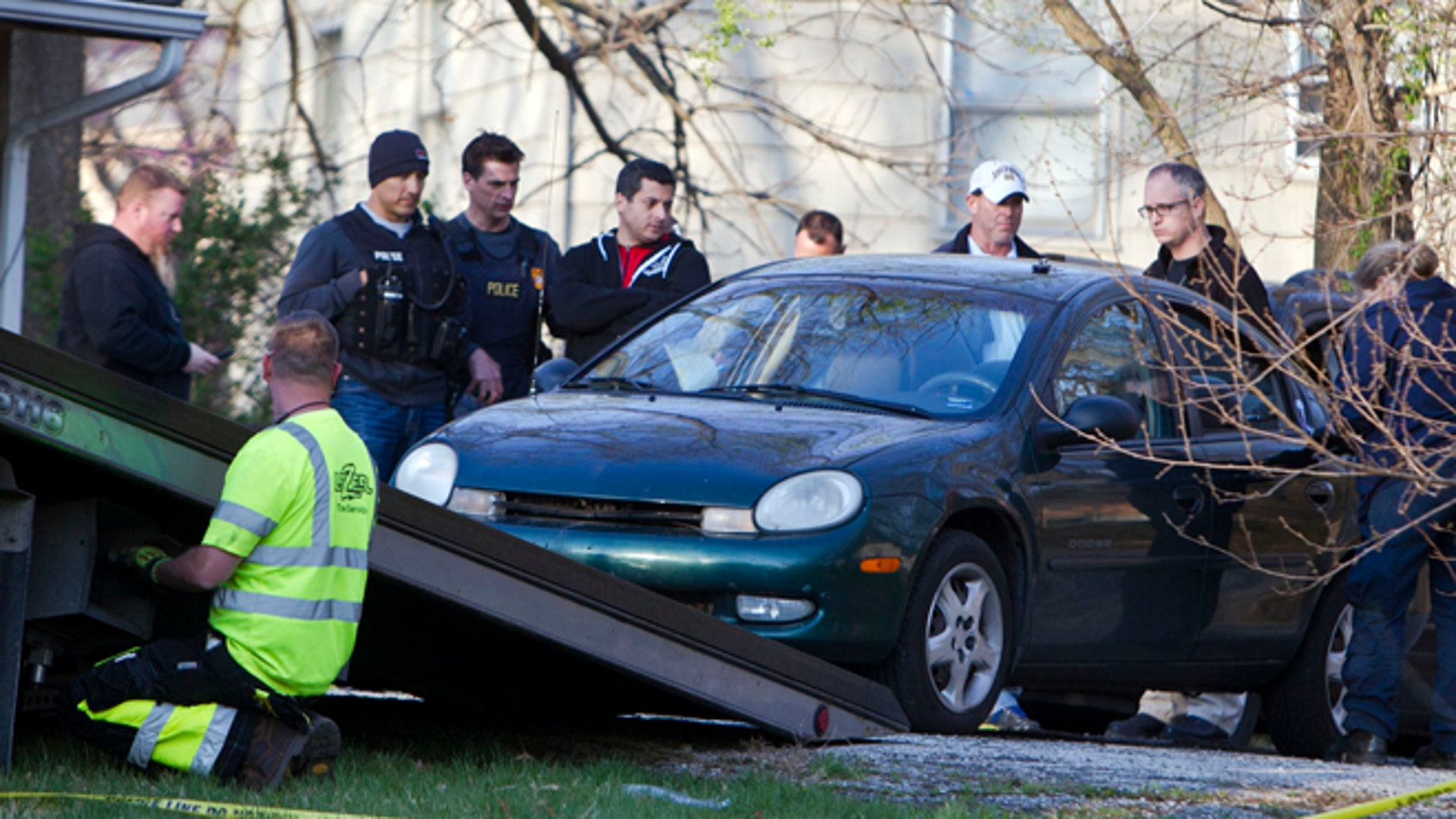 April 17: A car is removed by Kansas City police from the house, far right, of a Grandview man suspected in a series of shootings that have occurred on area roadways since early March, according to police.