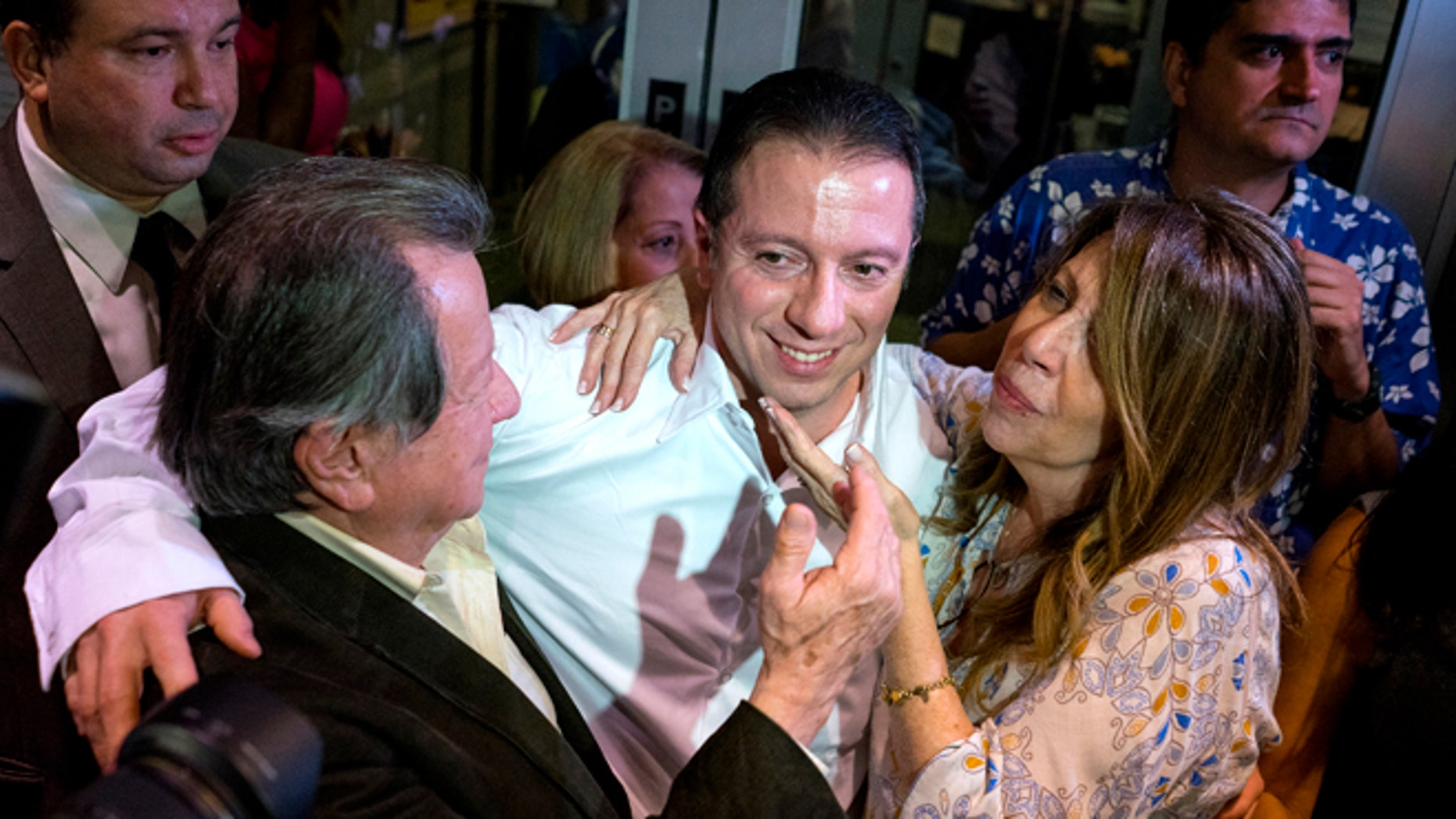 Johnny Hincapie, center, hugs his father Carlos Hincapie and mother Maria Hincapie as he leaves a court building, Tuesday, Oct. 6, 2015, in New York. Johnny Hincapie, imprisoned for a quarter-century in a notorious tourist killing, was granted a new trial and freed on Tuesday, after a judge overturned his conviction in a case that helped crystallize an era of crime and fear in the nation's biggest city. (AP Photo/Craig Ruttle)