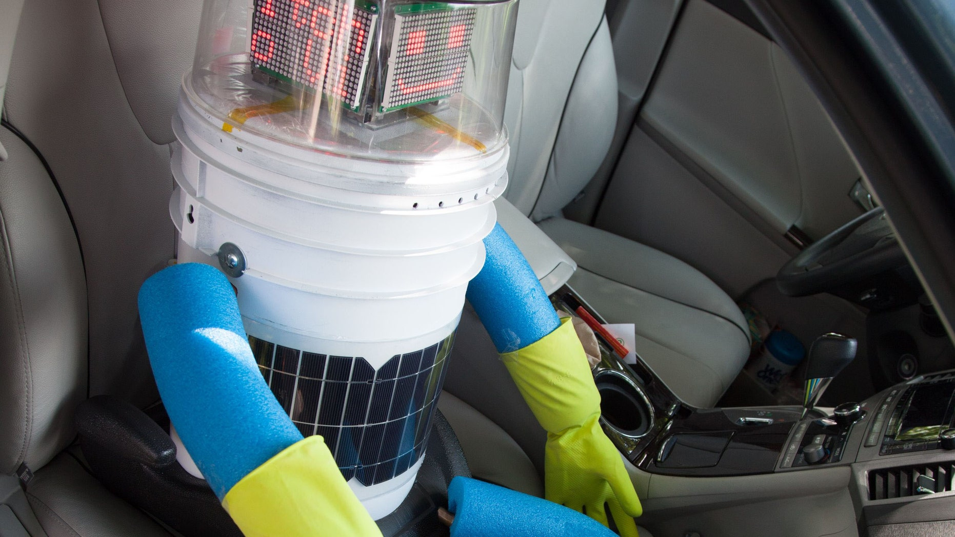 This undated photo made available by Ryerson University in Toronto on Thursday, Aug. 14, 2014 shows hitchBOT in a car. The talking robot that's been hitchhiking rides from strangers to travel from Canada's east to west coast is nearing the end of its journey. Its final destination is Victoria, British Columbia, Canada which its creators expect it to reach by Aug. 17, 2014. (AP Photo/Ryerson University)